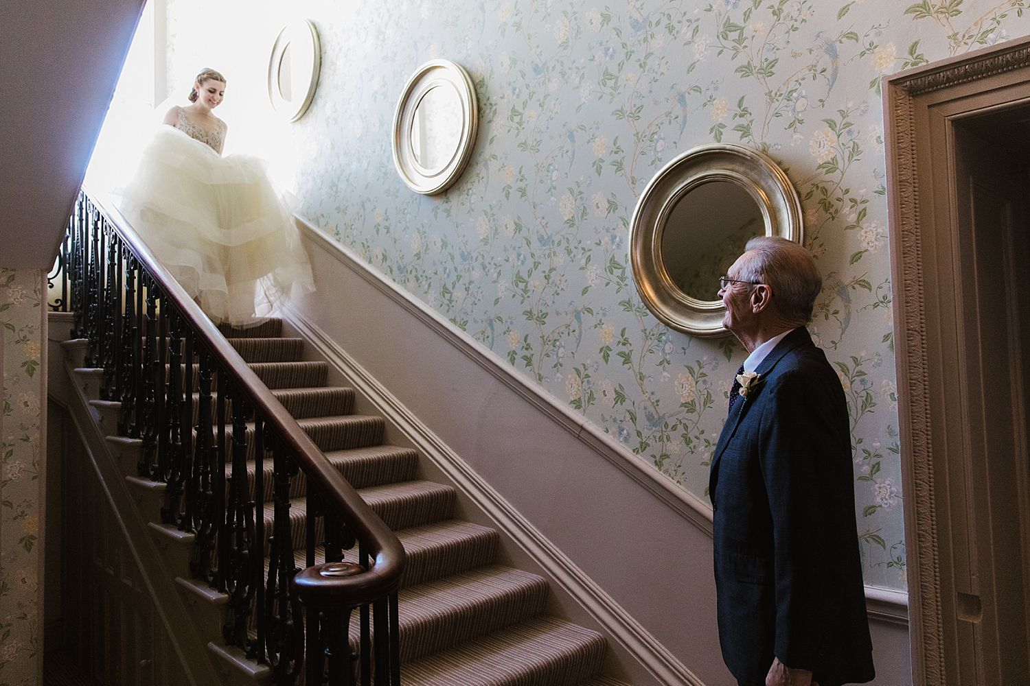 Bride descending stairs to brides father at the Laura Ashley Belsfield Hotel