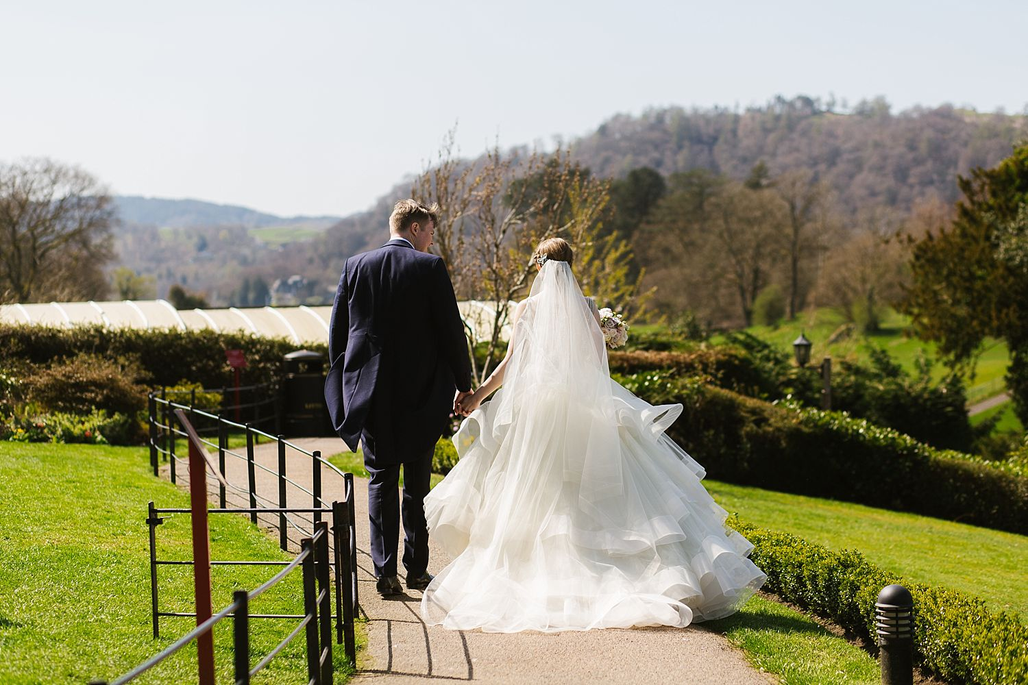 back view of brade and groom walking thrugh gardens of Laura Ashley Belsfield Hotel