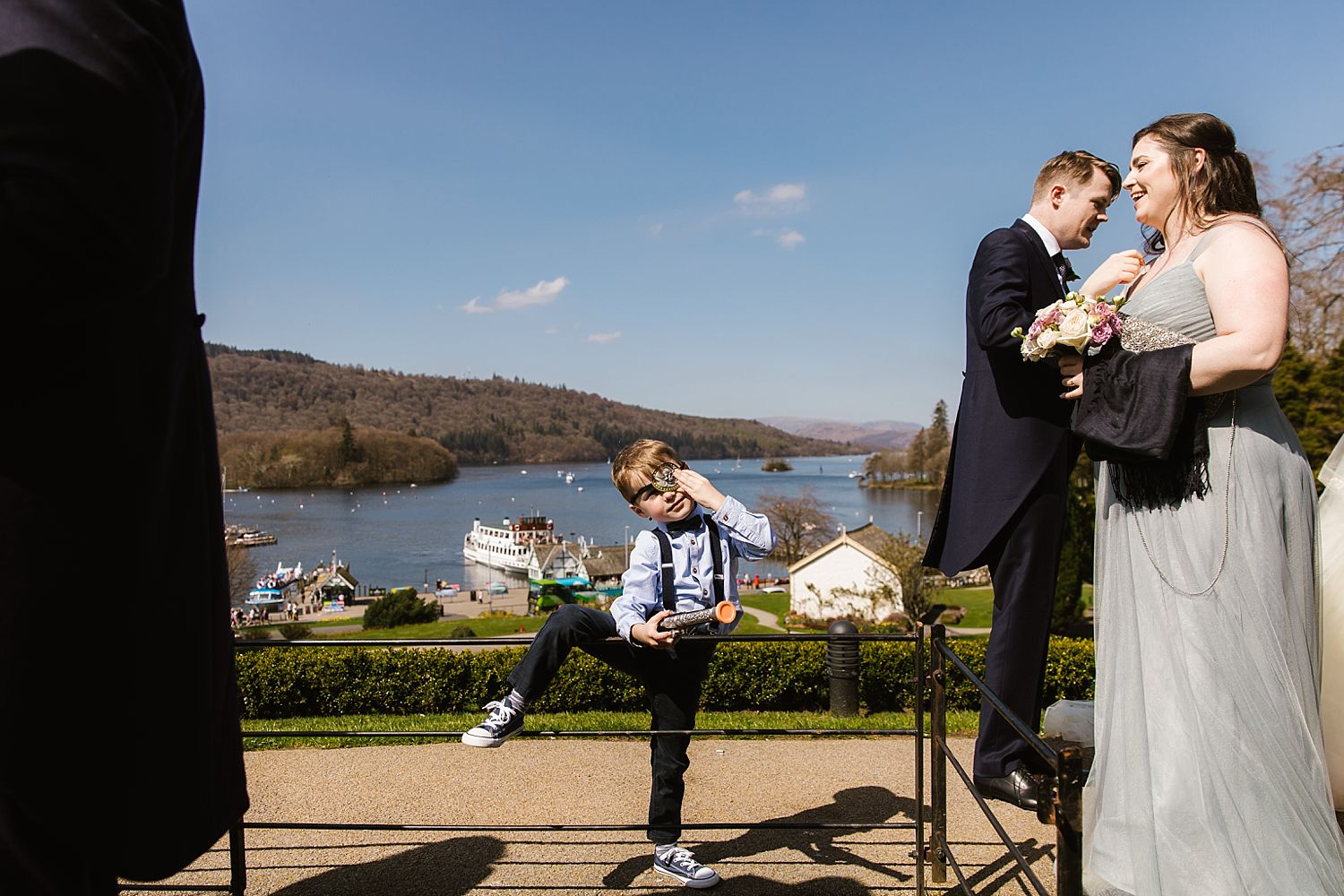 Small child playing and guests mingling at wedding reception with view of Lake Windermere