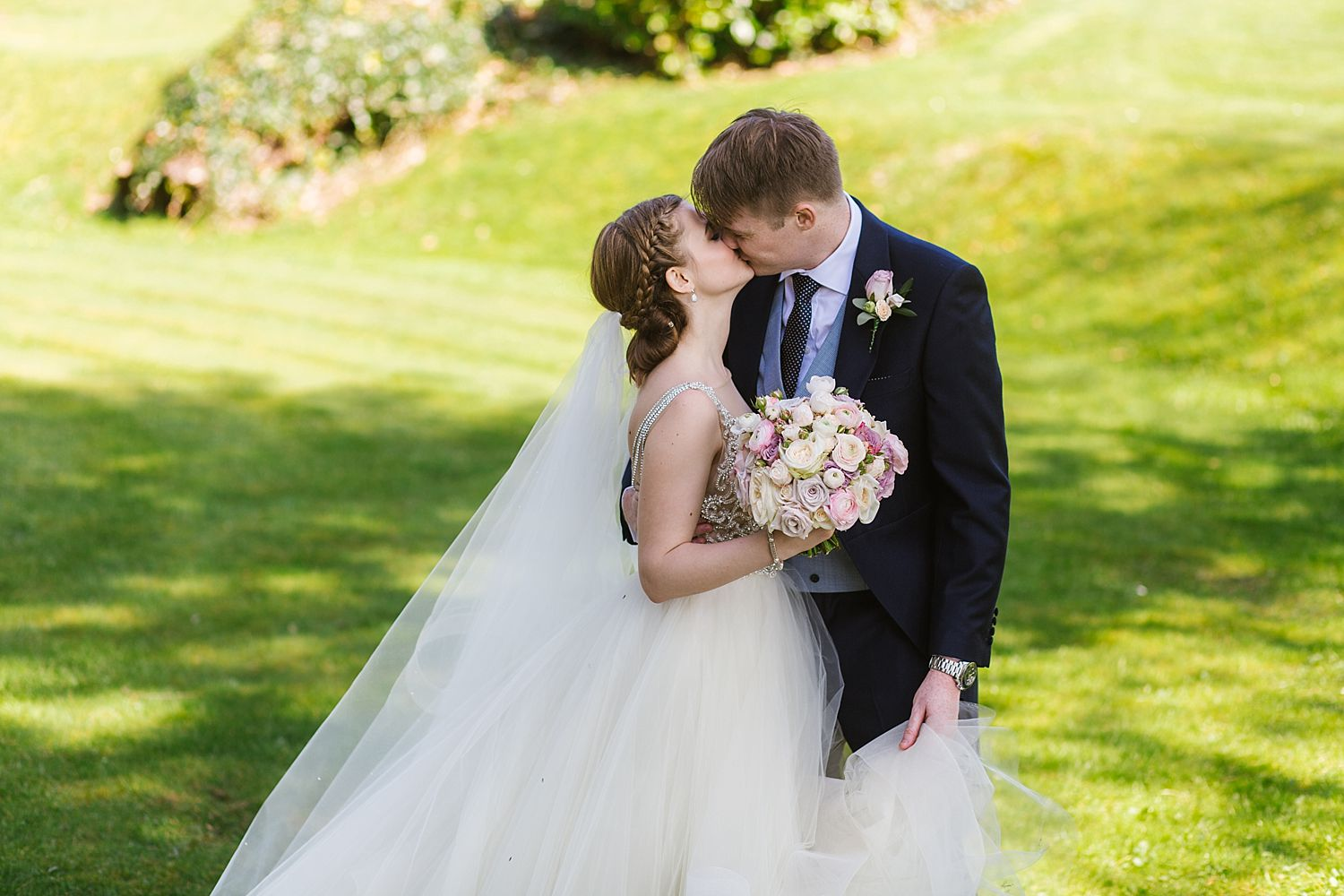 bride and groom kissing in gardens fo Laura Ashley Belsfield Hotel