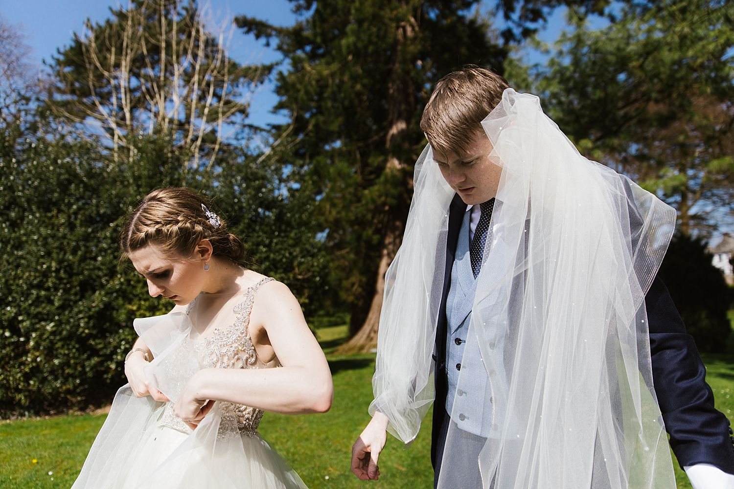 Bride rearranges dress, bride groom carries veil over his shoulders at Belsfield hotel wedding