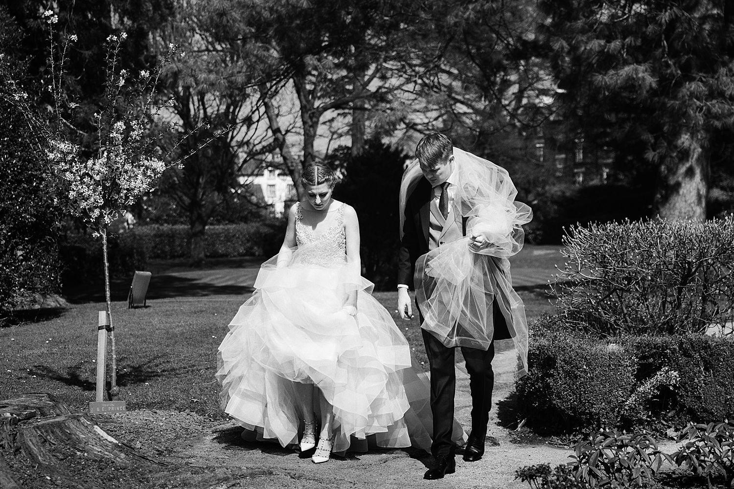 Bride and groom walking together, grrom holding veil in the grounds of the Belsield Hotel in Bowness on Windermere