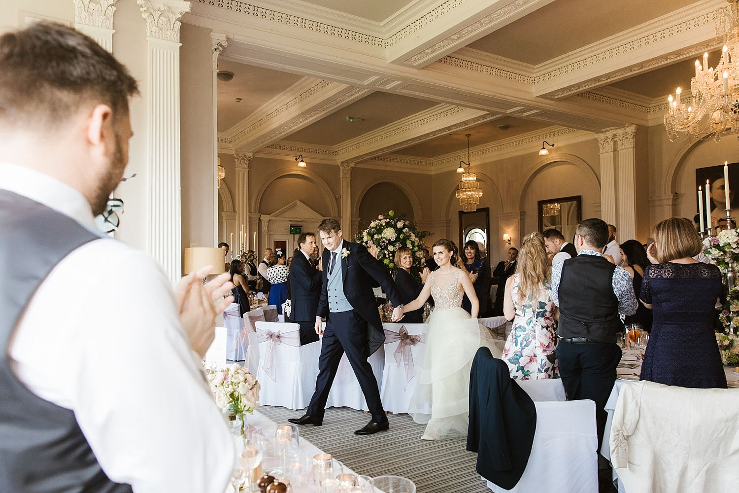 Bride and groom enter reception at Belsfield Hotel, holding hands.