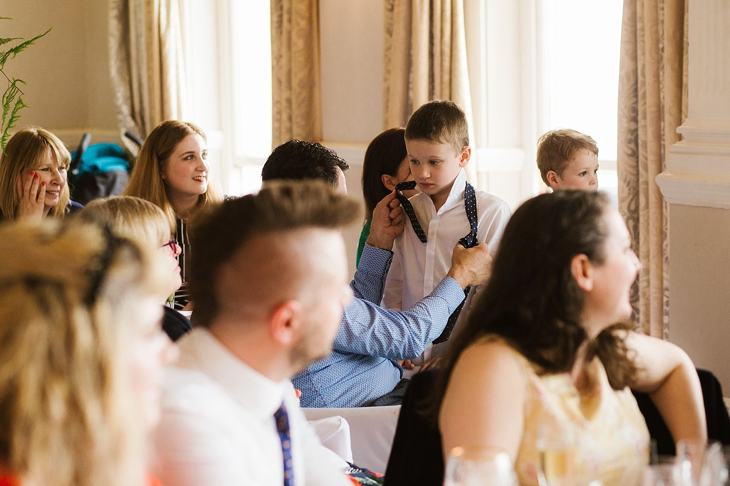 Guest adjusts young boy's tie during reception at Belsfield Hotel wedding