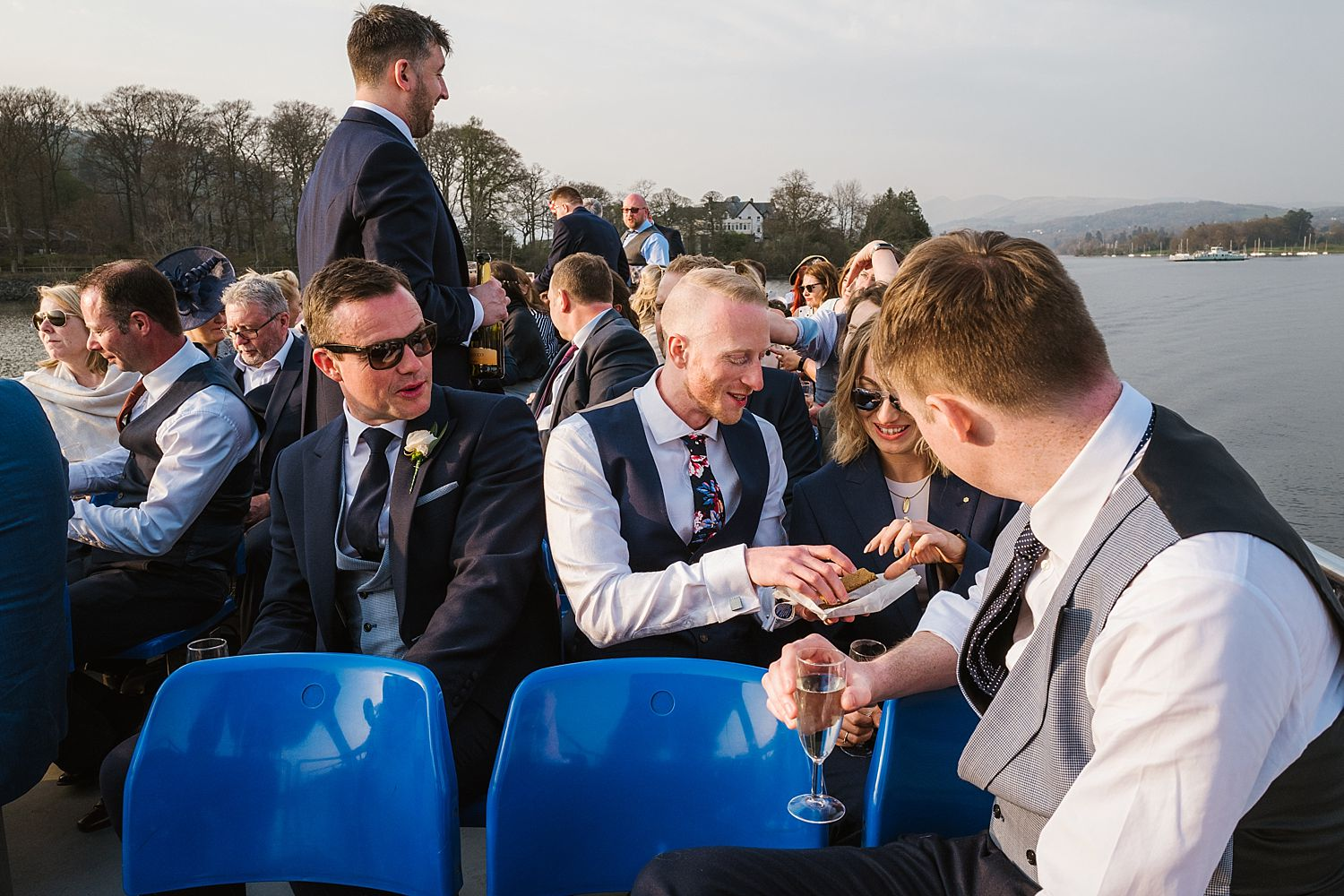 Guests sharing nibbles on board Lake Windermere cruiser after Belsfield Hotel wedding