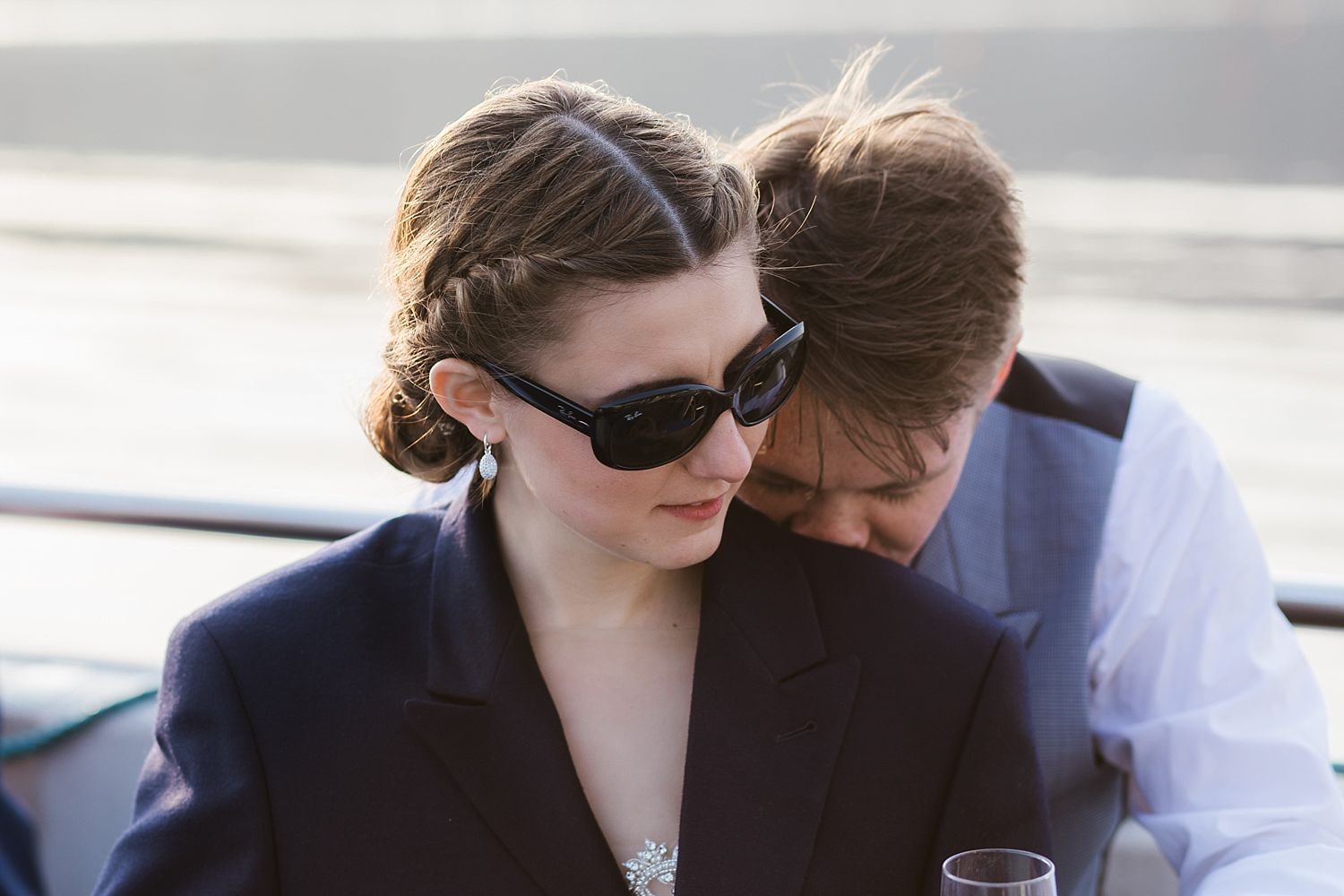 Groom nuzzles bride, bride in grroom's jacket and sunglasses during cruise on Lake Windermere after Belsfield Hotel wedding