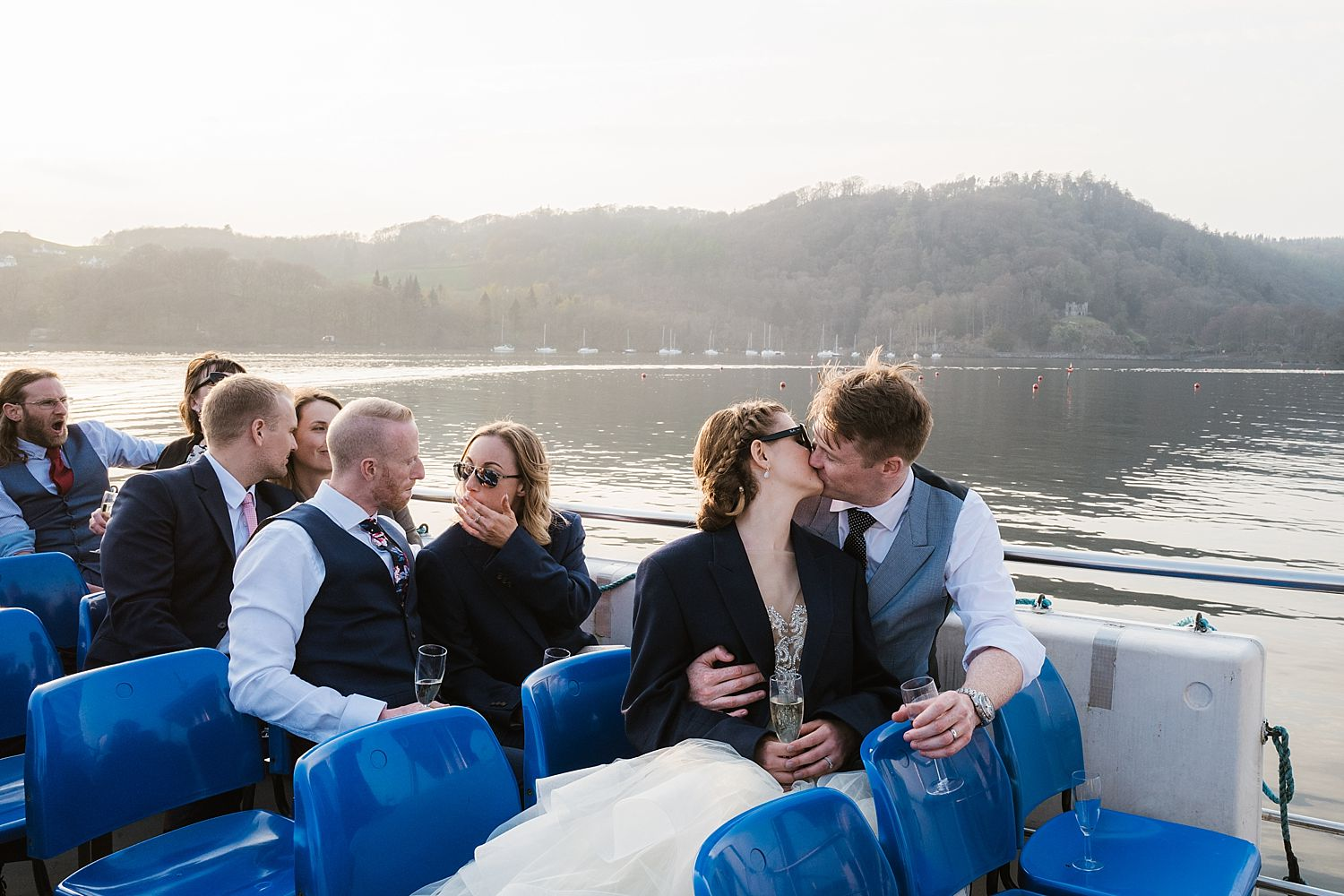 Bride and groom kissing on board cruiser with view of Lake Windermere in background, after Laura Ashley, Belsfield Hotel wedding