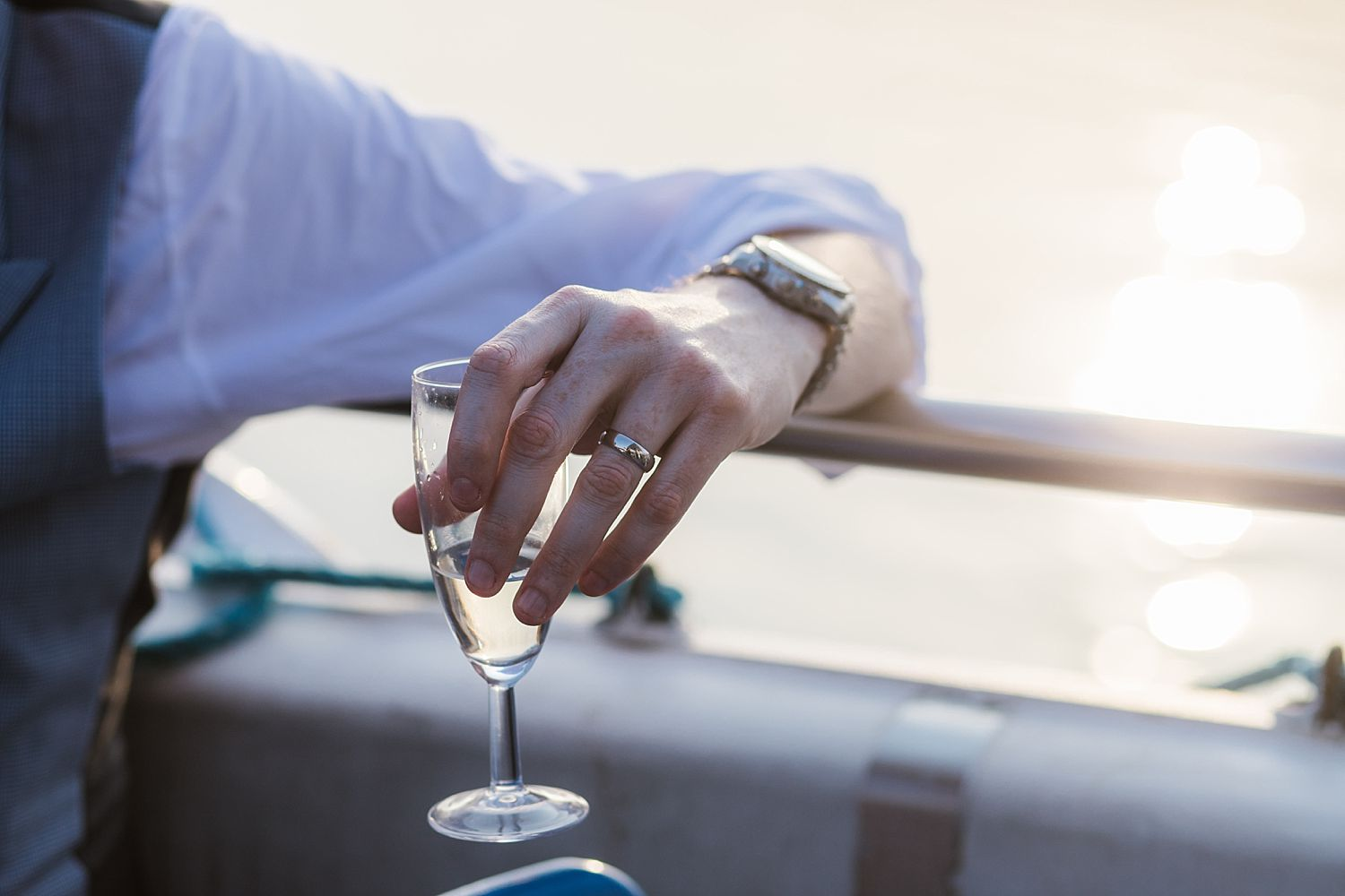 Close up of bridegroom's ring as he holds champagne glass on board Windermere cruiser after Belsfield Hotel wedding