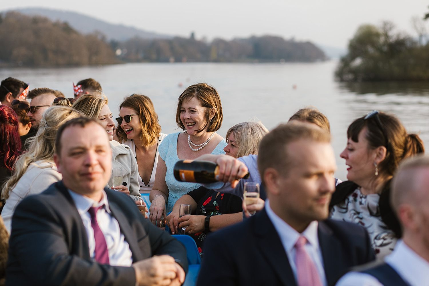Wedding guests enjoying champagne on Lake Windermere cruiser after Belsfield Hotel wedding