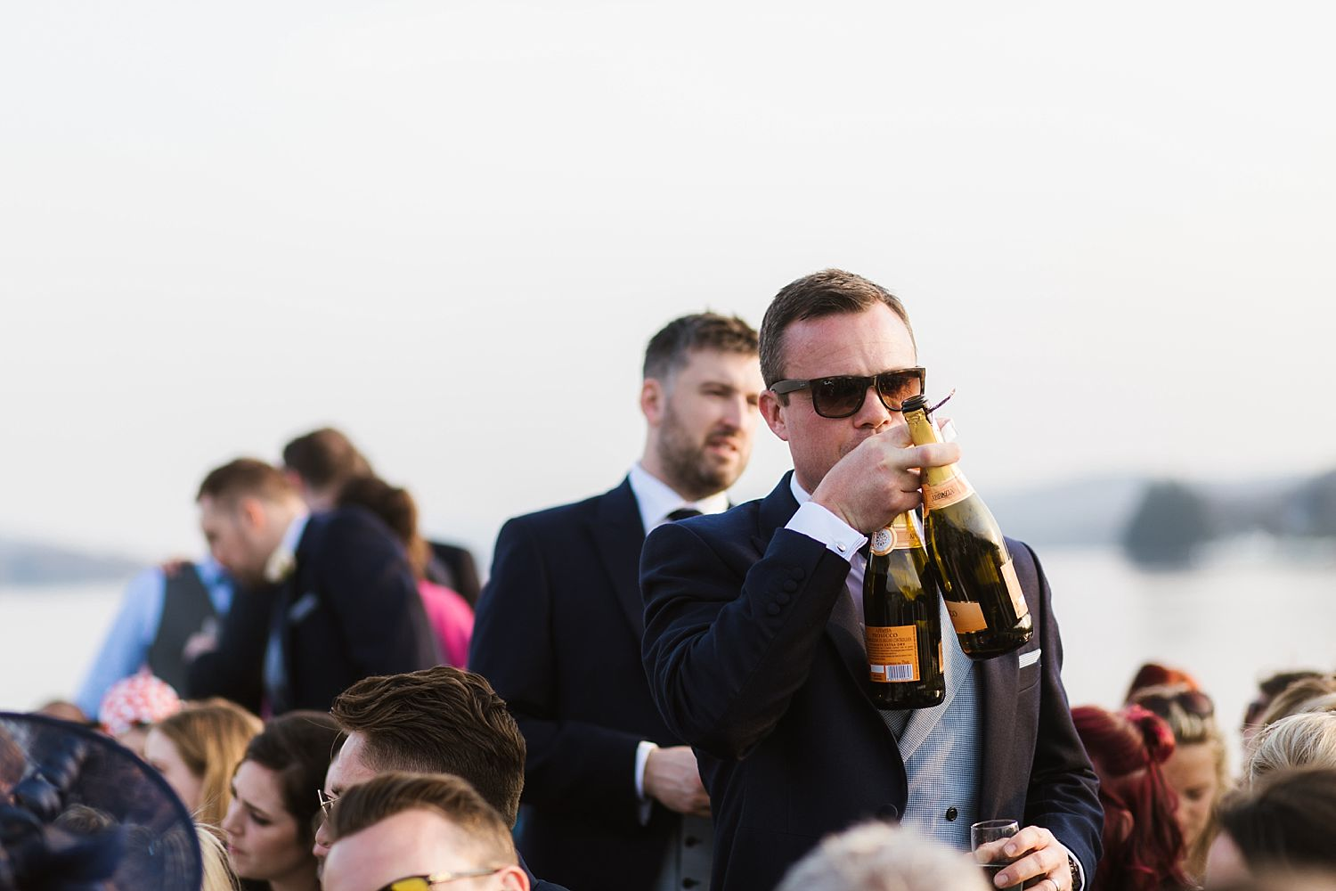 Best man with two bottles of champagne at Lake District wedding cruise