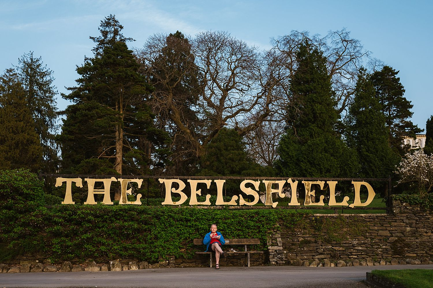The Belsfield Hotel sign with tourist enjoying the view of Lake Windermere