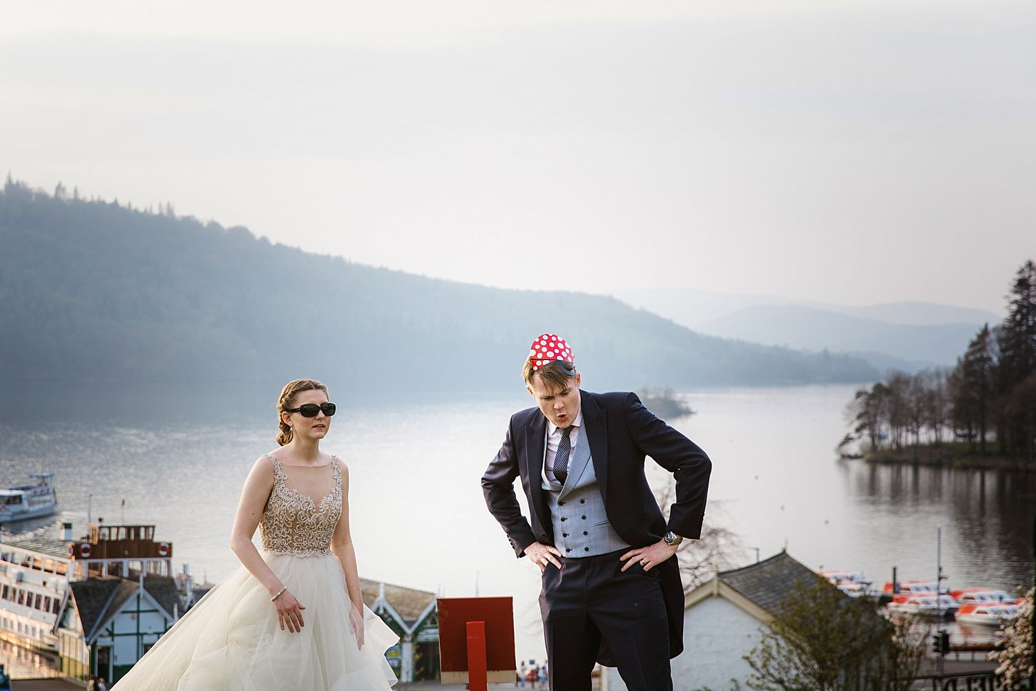 Bridegroom wearing pirate hat with view of Lake Wndermere behind, from the Laura Ashley Belsfield Hotel in Bowness on Windermere