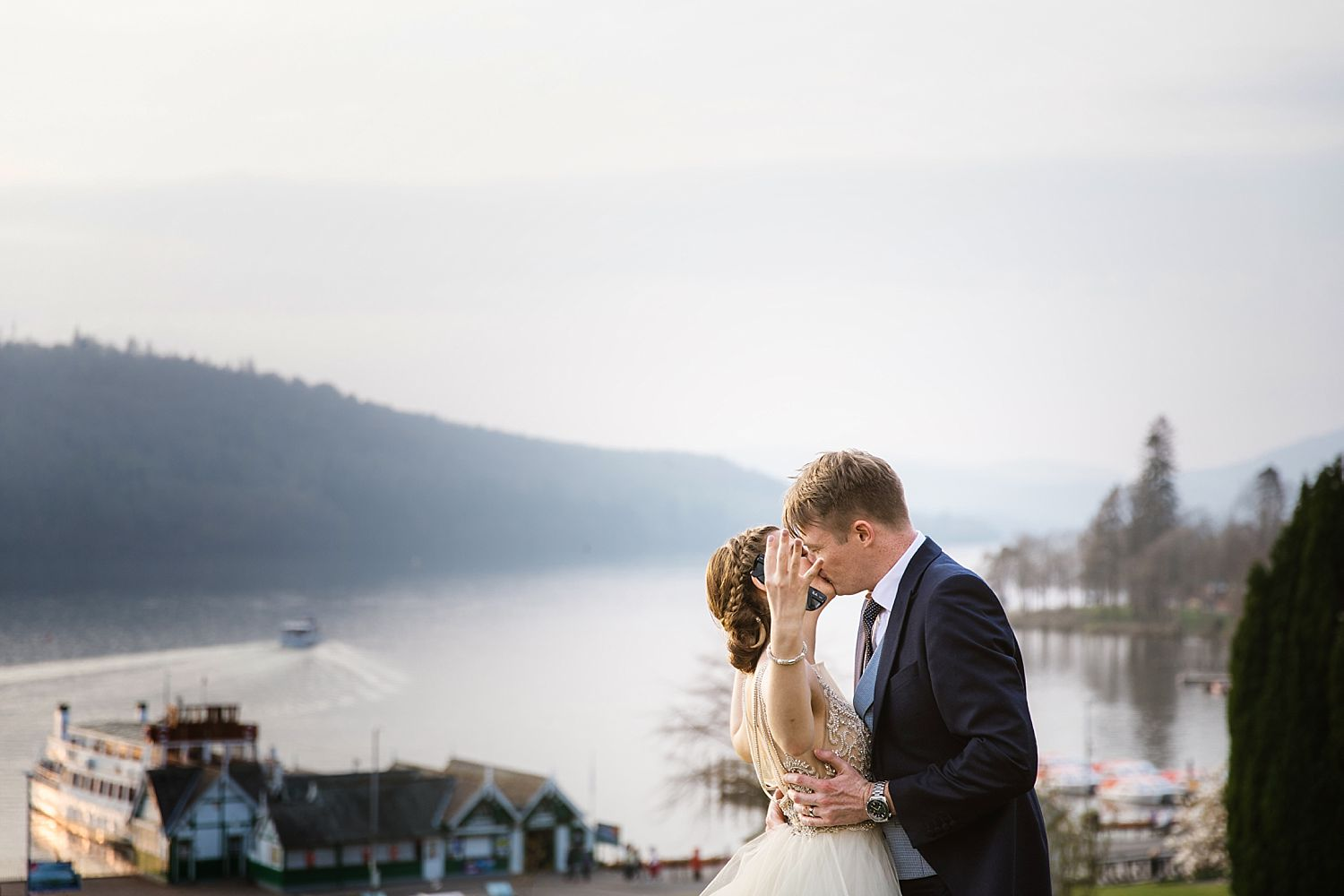Bride and groom kiss, broide's arms outstretched with view of Lake Windermere in background, taken from Belsfield Hotel wedding