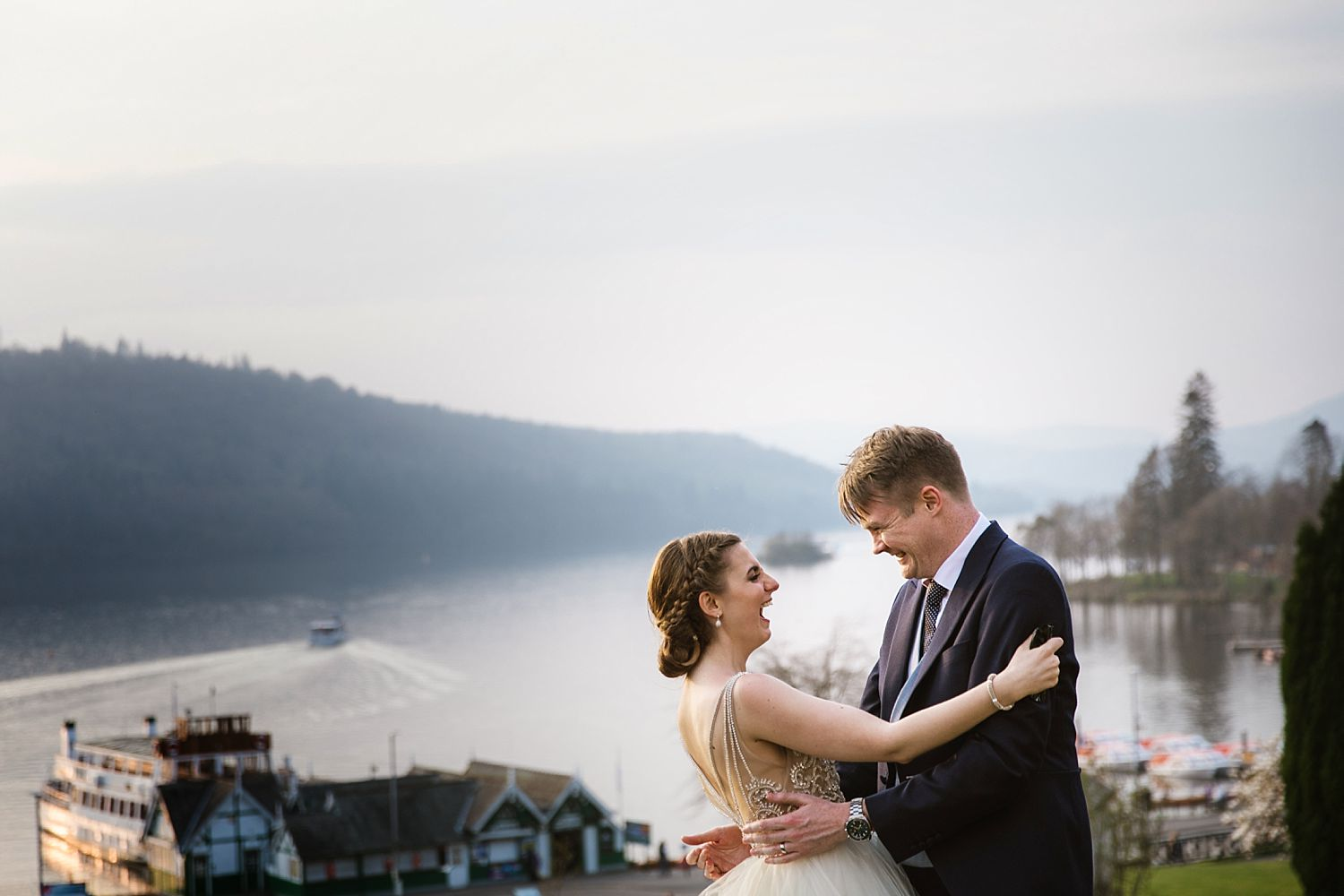 Bride and groom laughing together with view of Windermere Lake at Beslfield Hotel wedding