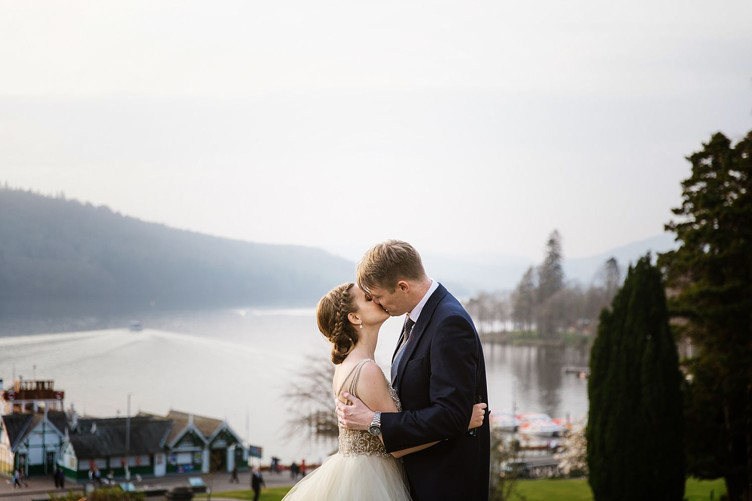 Bride and groom kissing with view of Lake Windermere at Belsfield Hotel wedding