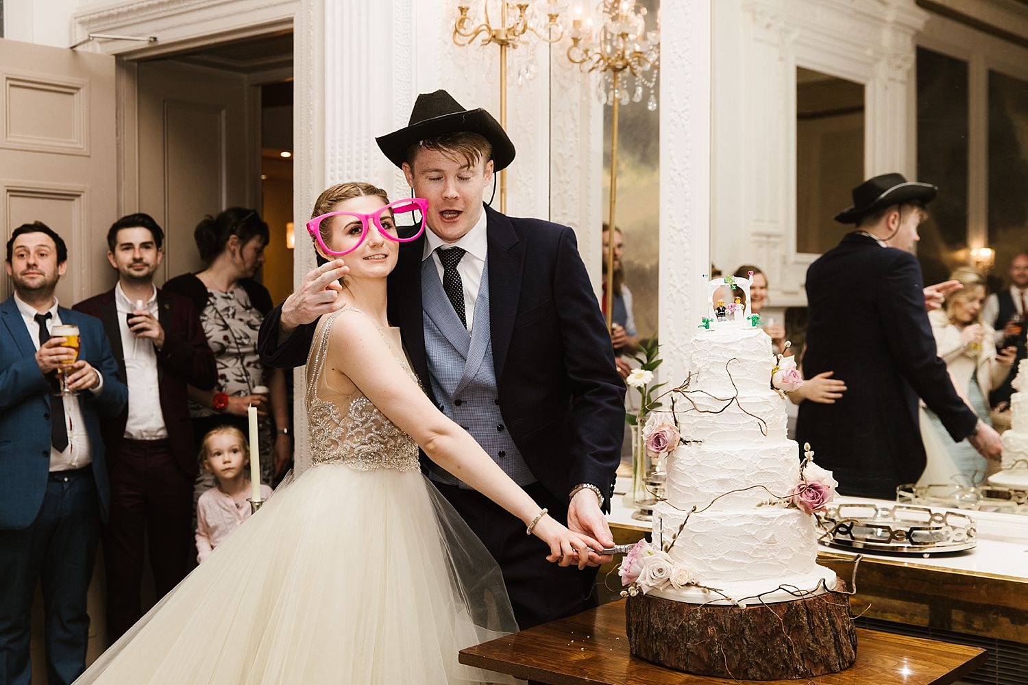 groom in cowboy hat and Bride in oversized pink glasses cut the wedding cake at their Lake District wedding