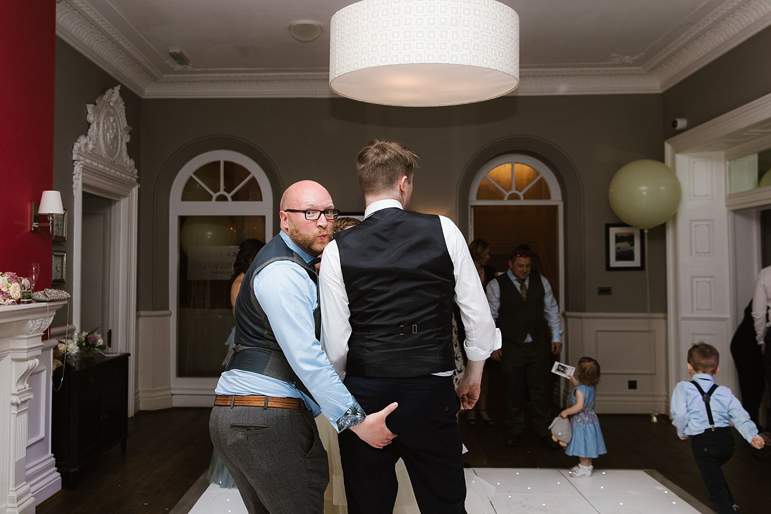 Guest grabs bridegrooms bum at evening reception at Lake District wedding venue, Belsfield Hotel