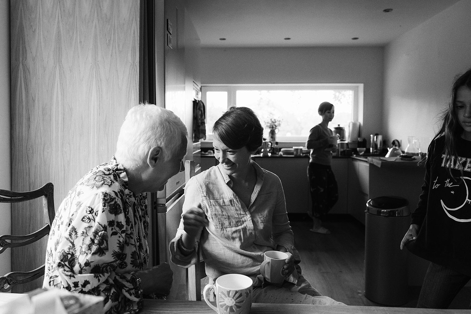 Bride and her father share a joke in the kitchen durong build up to Park House Barn wedding