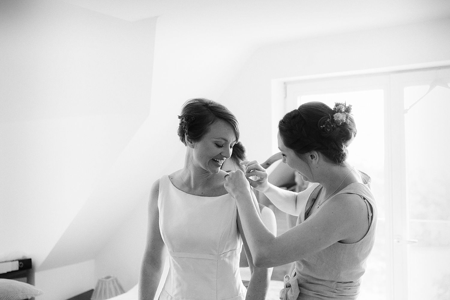 Bridesmaid helping bride with dress for her wedding at Cumbria wedding venue, Park House Barn