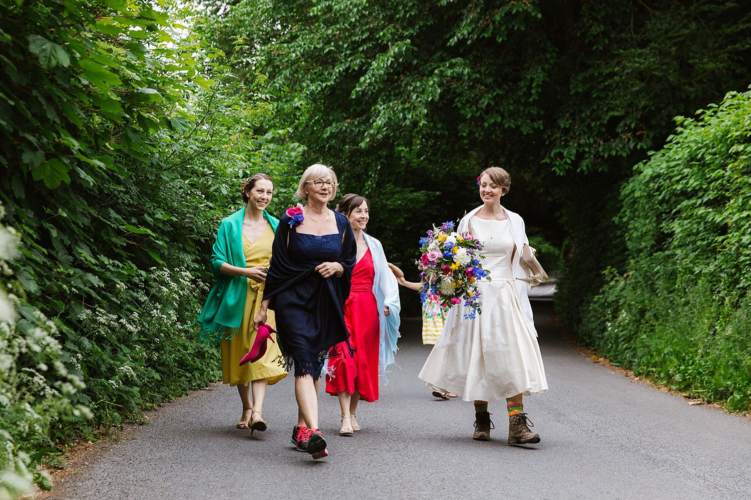 Bride, her mum and attendants wearing walking boots, walking to wedding at Park House Barn in Cumbria