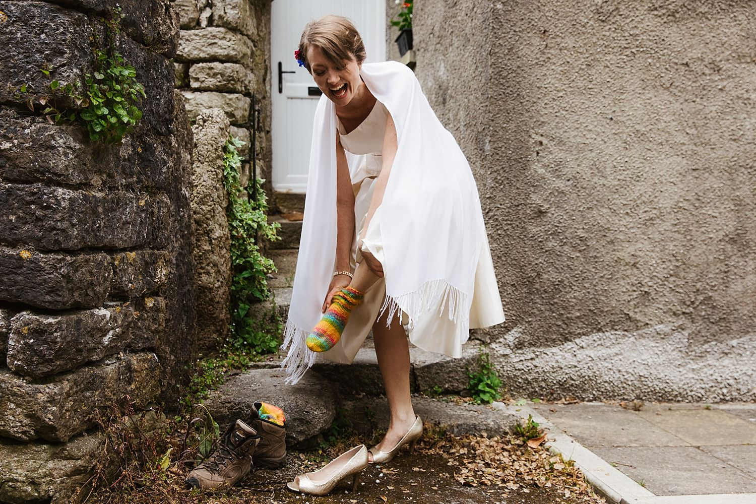 Bride changes into wedding shoes at entrance to Park House Barn wedding