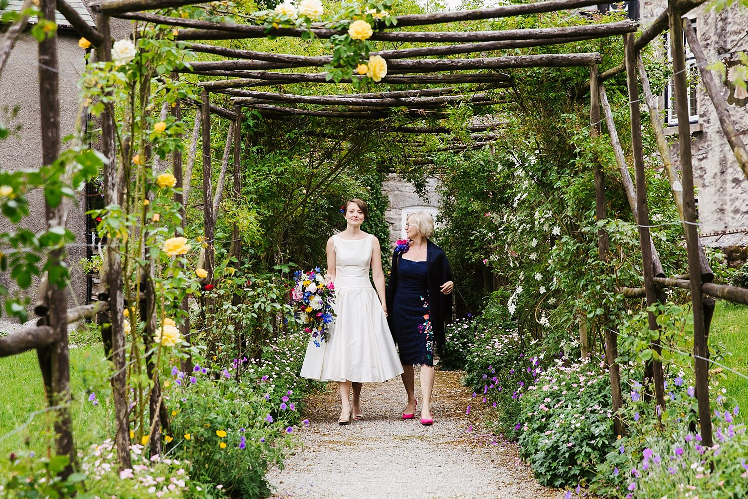 Bride and mum walk through floral pergolas for wedding at Park House Barn Heversham