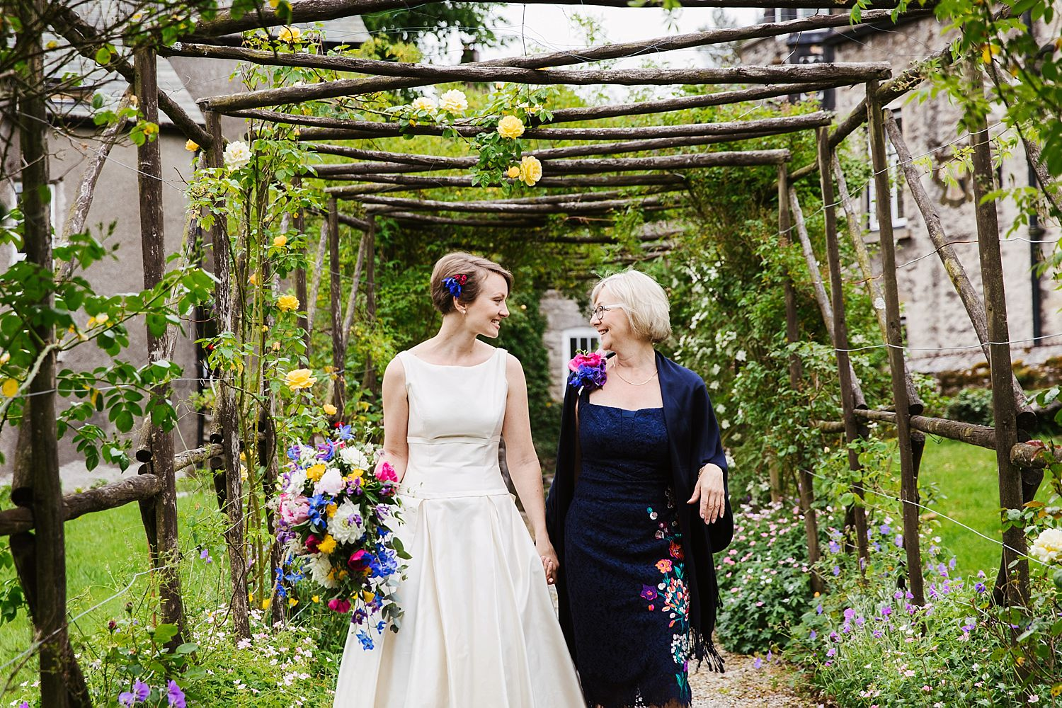 Bride and her mum, exchange a smile as they walk through floral pergola to wedding at Park House Barn in South Lakeland. Floristry by Carmen