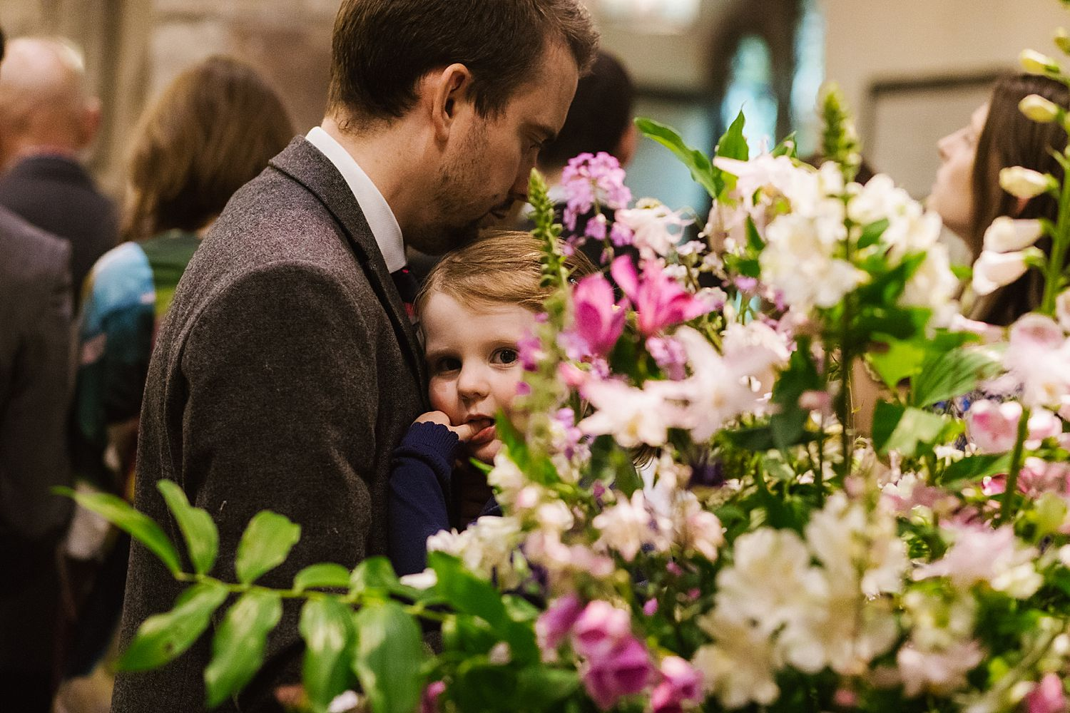 small child peeping through floral arrangement, Floristry by Carmen, at Park House Barn wedding