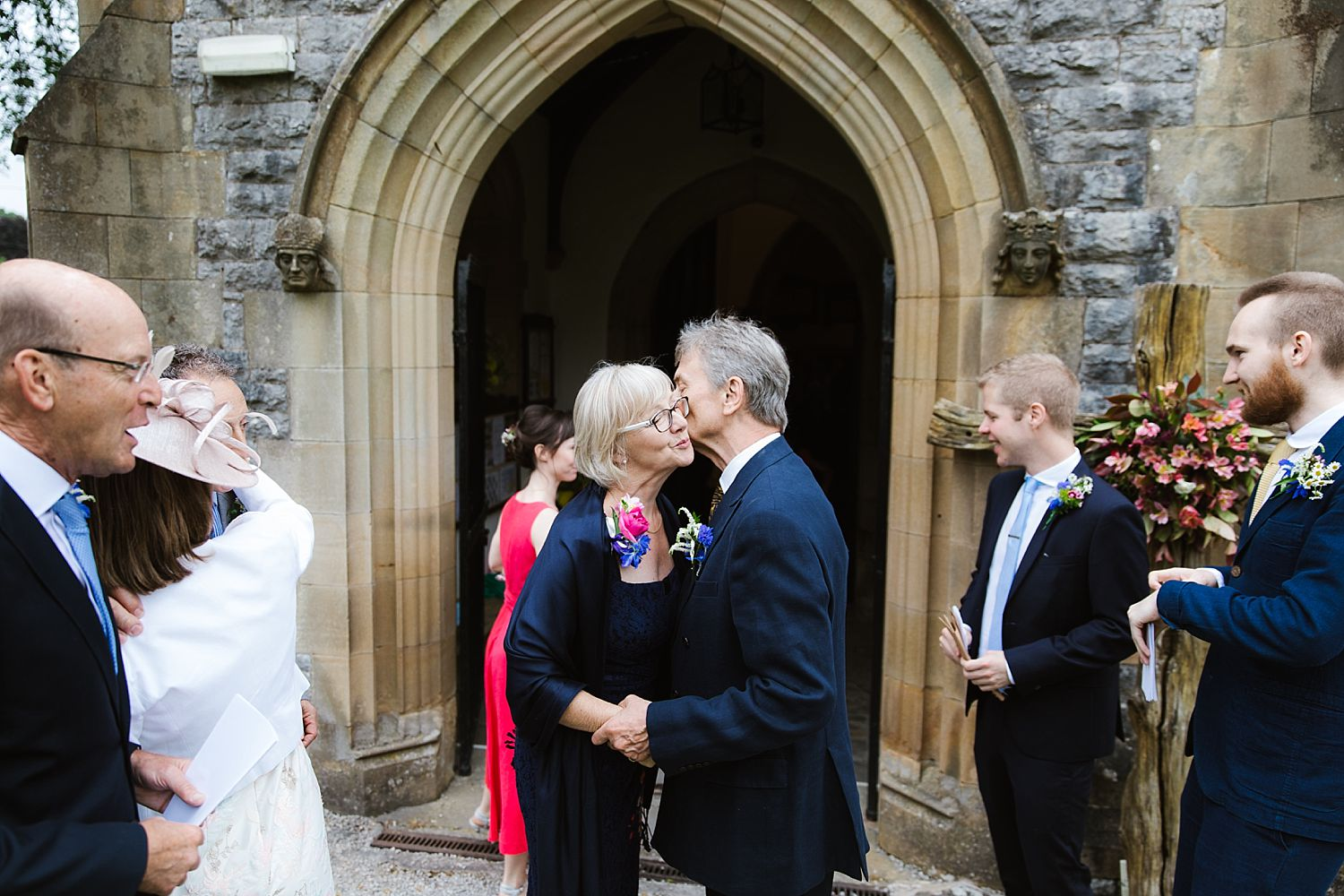 Guests exchange a kiss outside church at Cumbria wedding, Park House Barn
