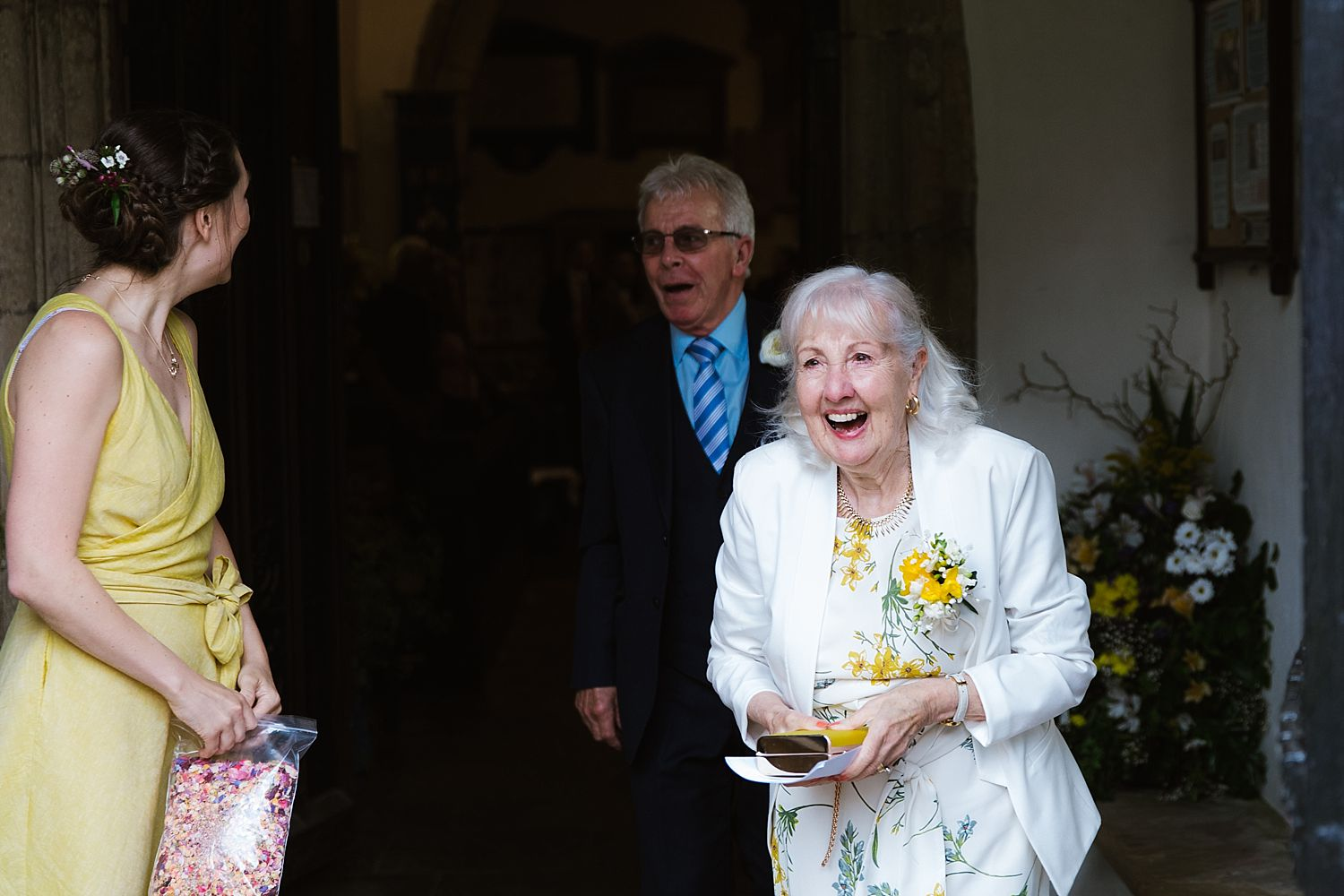Laughing guests leave church at Heversham wedding, Park House Barn