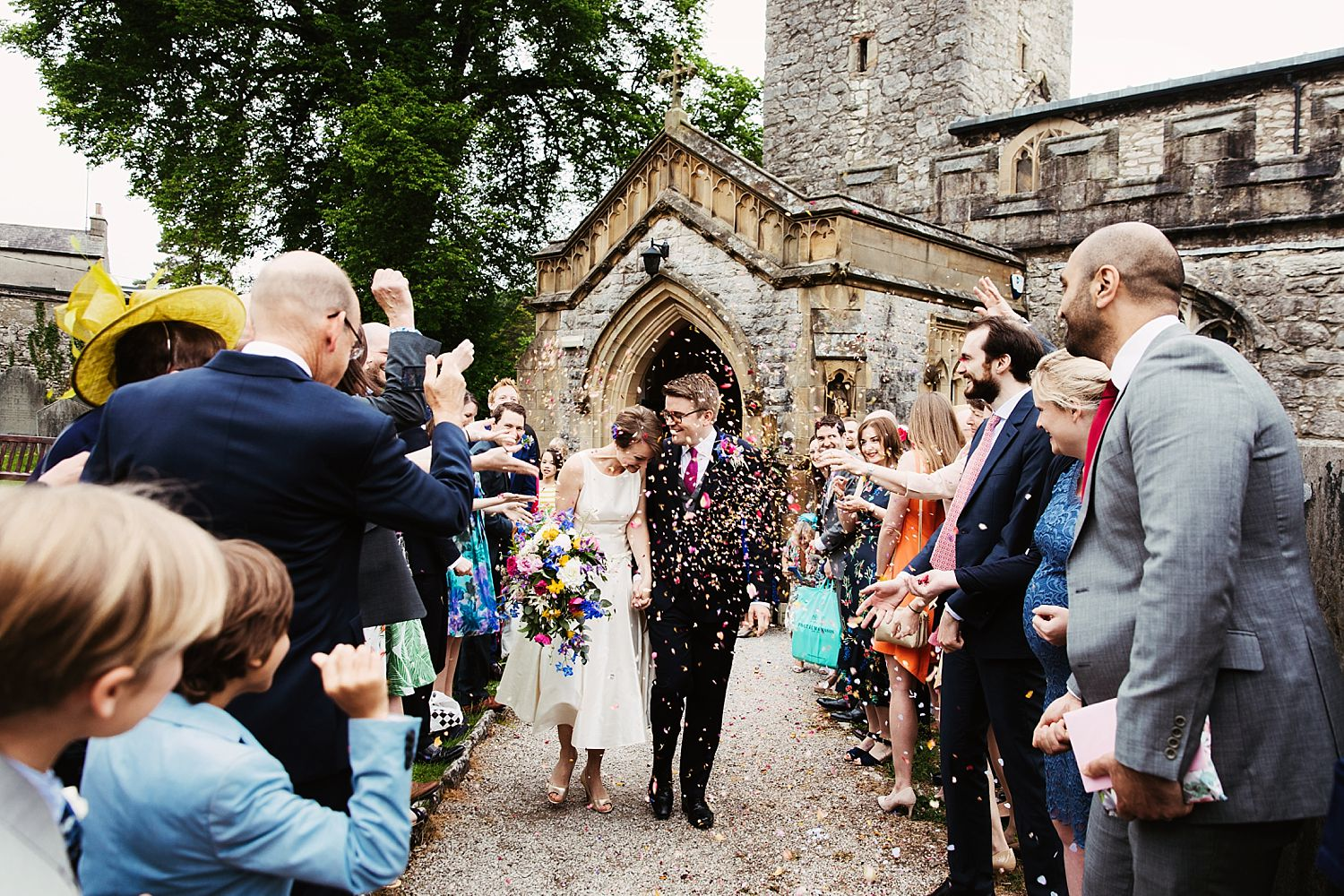 Bride and groom walk through confetti shower outside church for Park House Barn wedding in Heversham