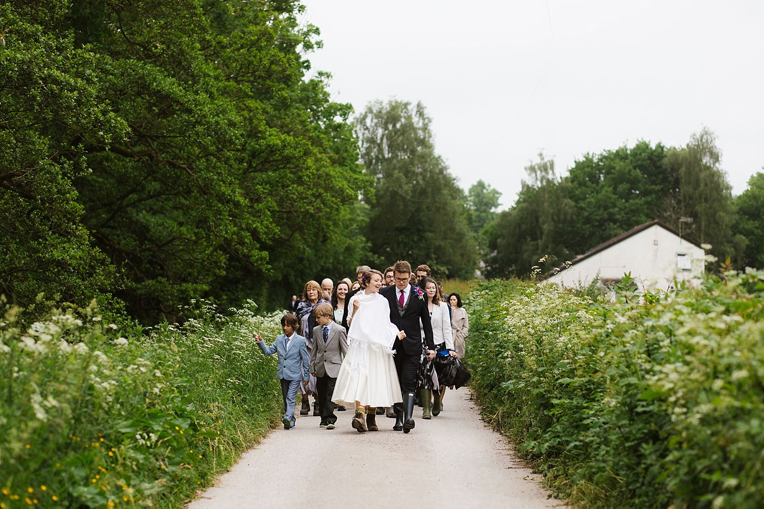 Bride and groom in wellies and walking boots, walk to reception at Park House Barn Milnthorpe