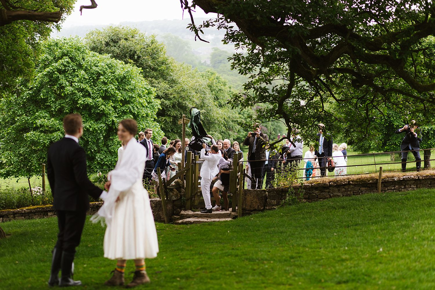 Bride and groom wait for wedding guests to come through kissing gate at wedding at Park House Barn in Heversham Cumbria