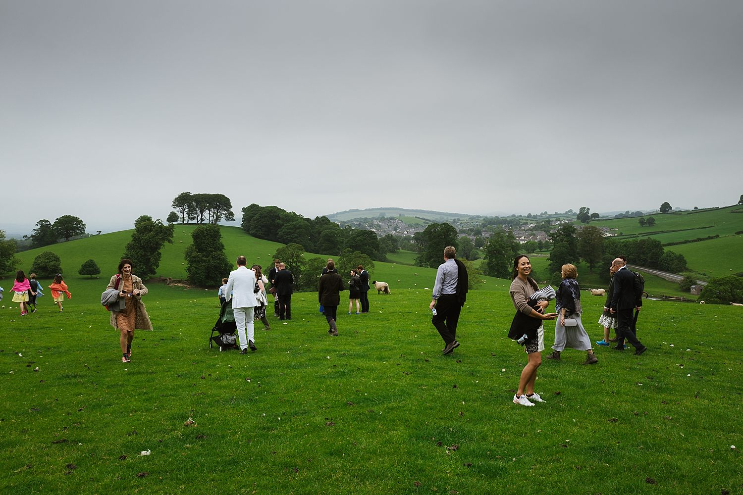 Guests crossing field towards wedding venue in South Lakeland, Park House Barn