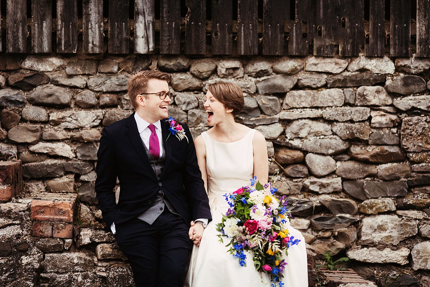Bride and groom giggling against wall of Park House Barn, wedding venue in Heversham, Floristry by Carmen