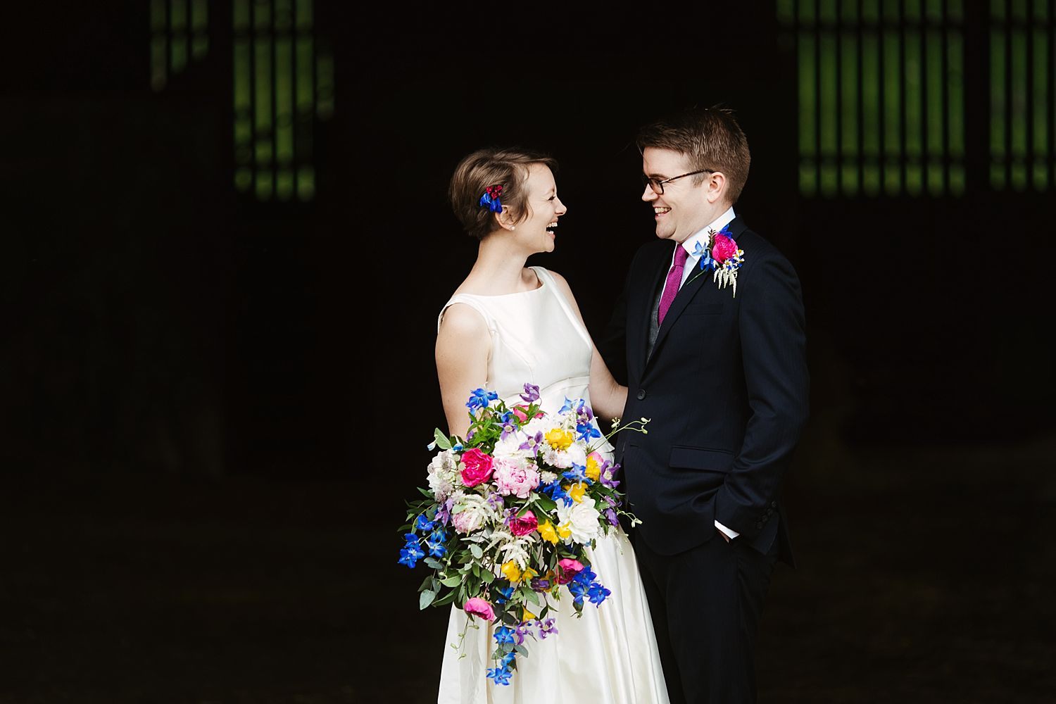 Bride and groom laughing together outside wedding reception venue, Park House Barn. Floristry by Carmen