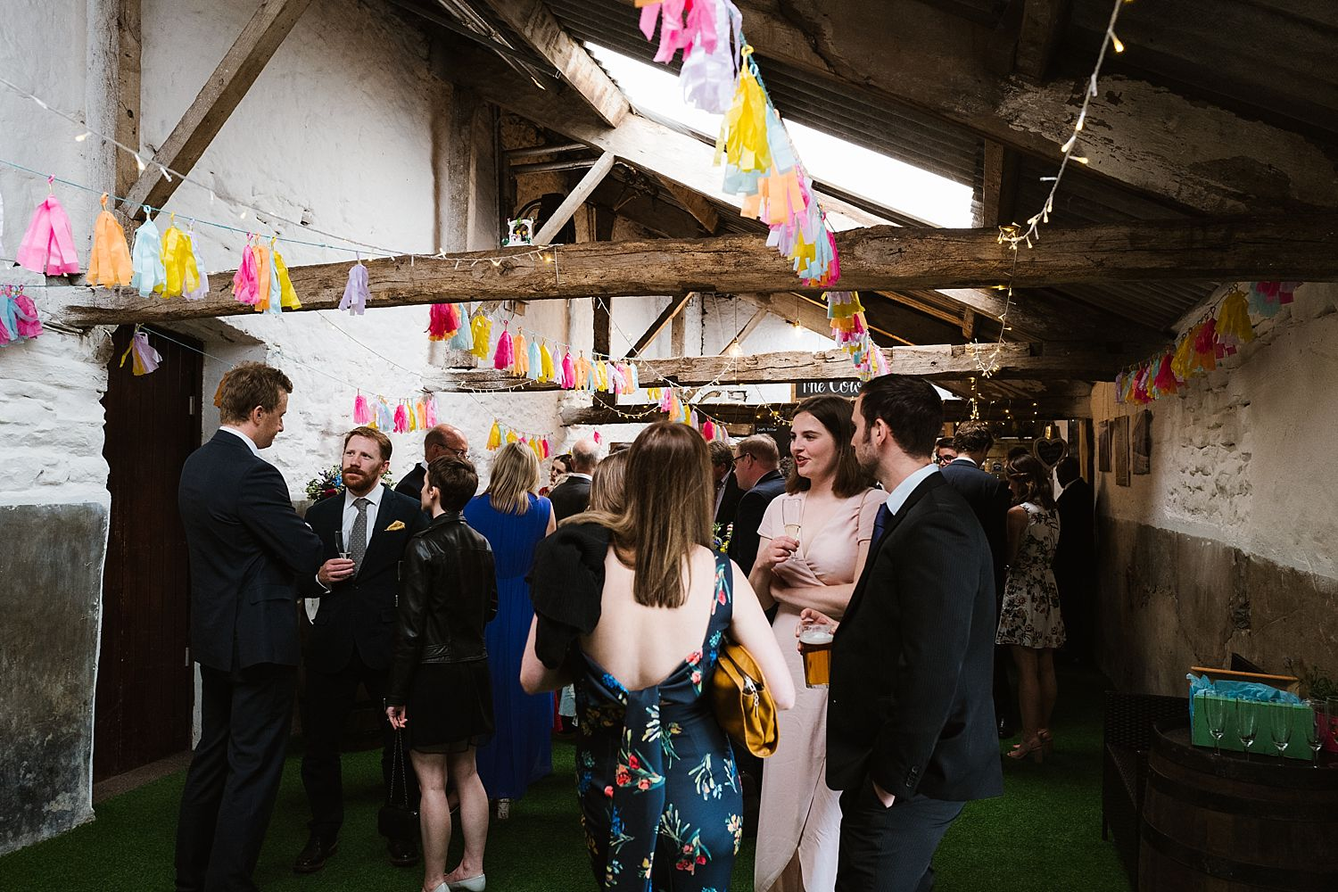 Guests mingling in the big barn at South Lakes wedding venue Park House Barn