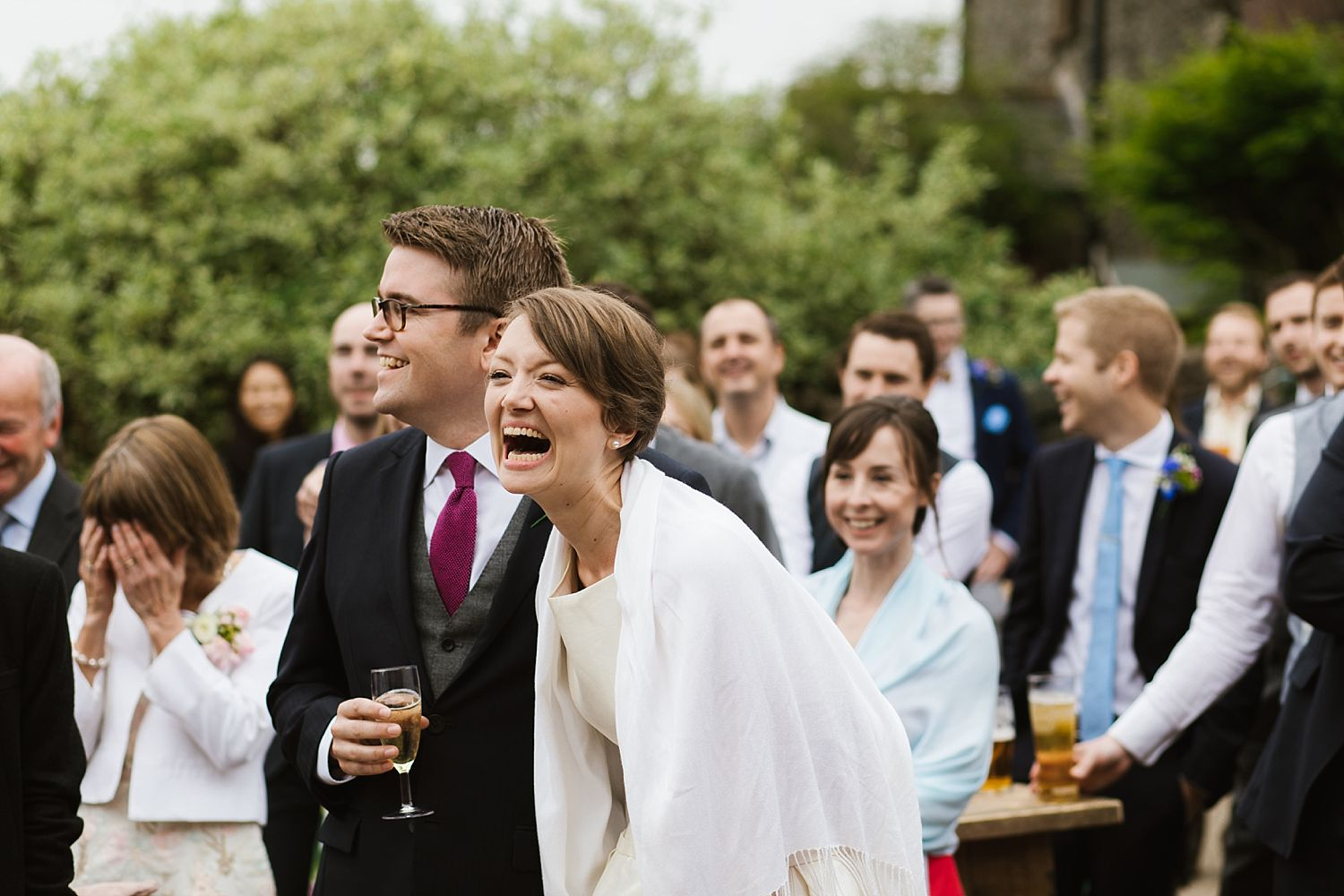 Bride and groom laughing with guest at Heversham wedding, Park House Barn
