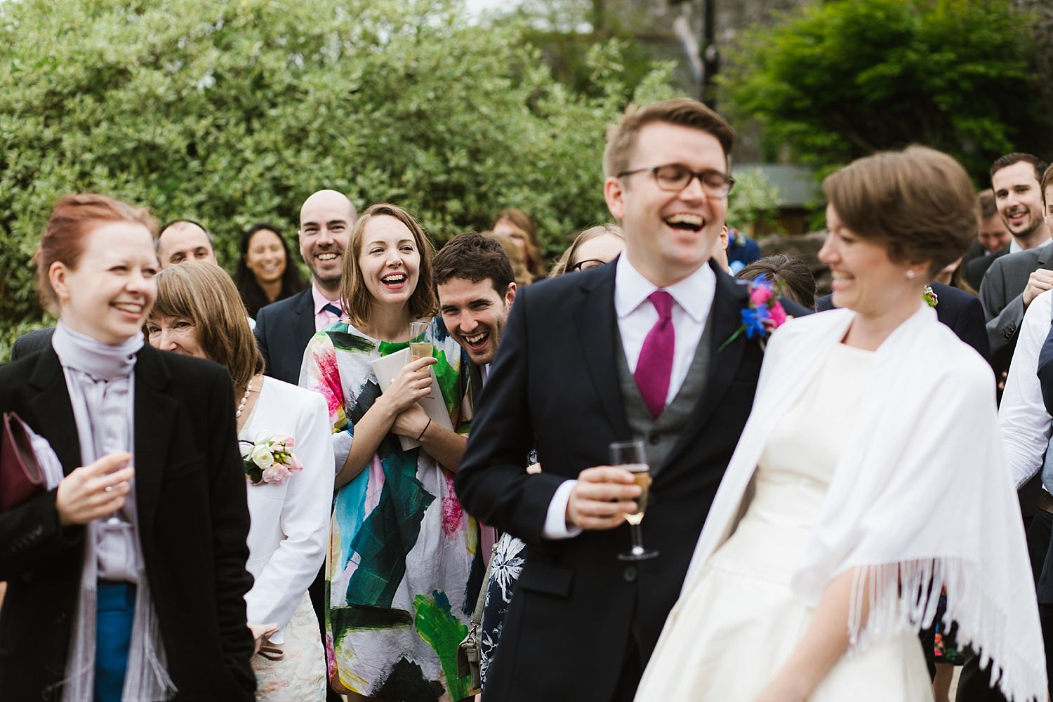 Groom and bride, sharing a joke with guests at Park House Barn wedding, Heversham