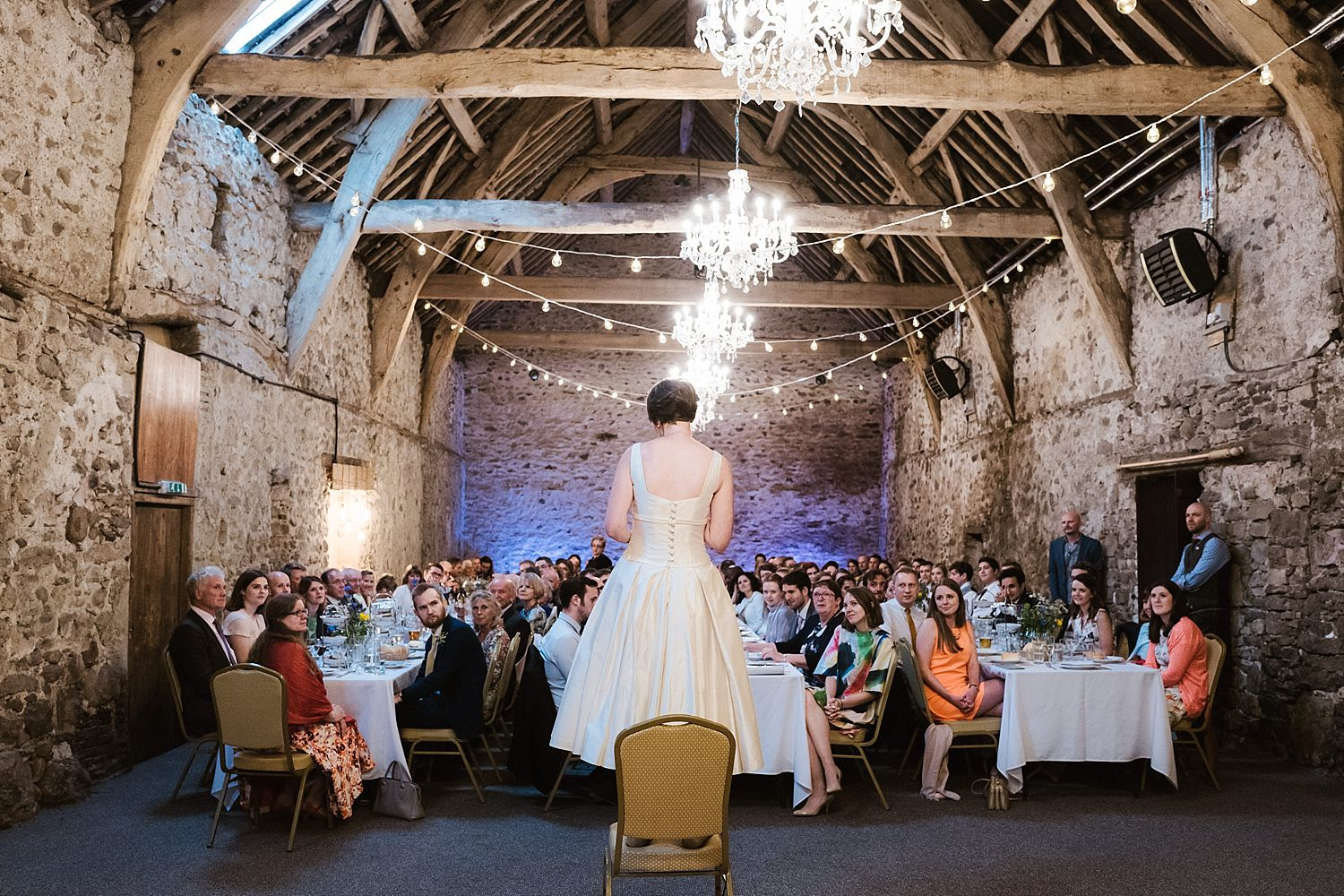 Back view of bride making speech to seated guests at wedding reception at Park House Barn, Heversham