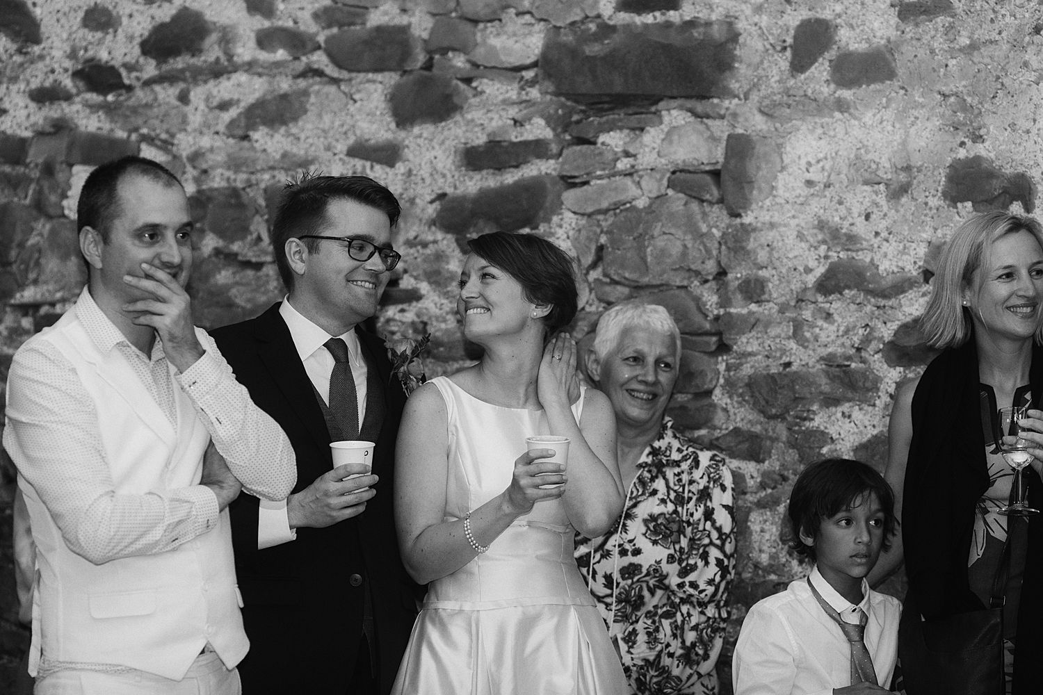 Bride and grrom with coffee cups and guests at Park House Barn in Cumbria