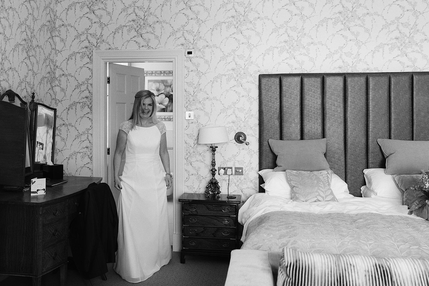 Smiling bride walks into bedroom for her Lake District wedding at Storrs Hall