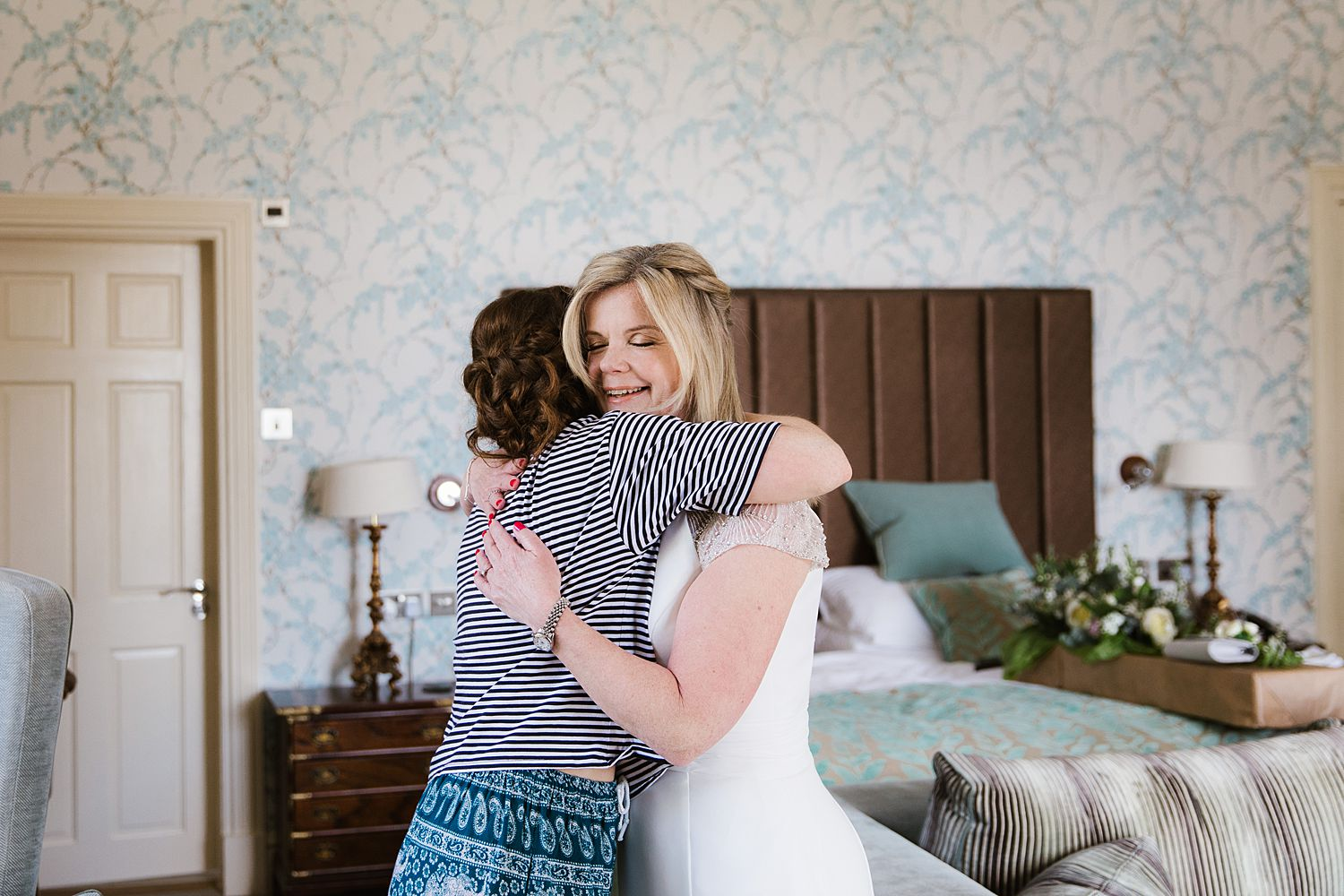 Bride embraces her bridesmaid at Storr Hall Wedding, Lake District