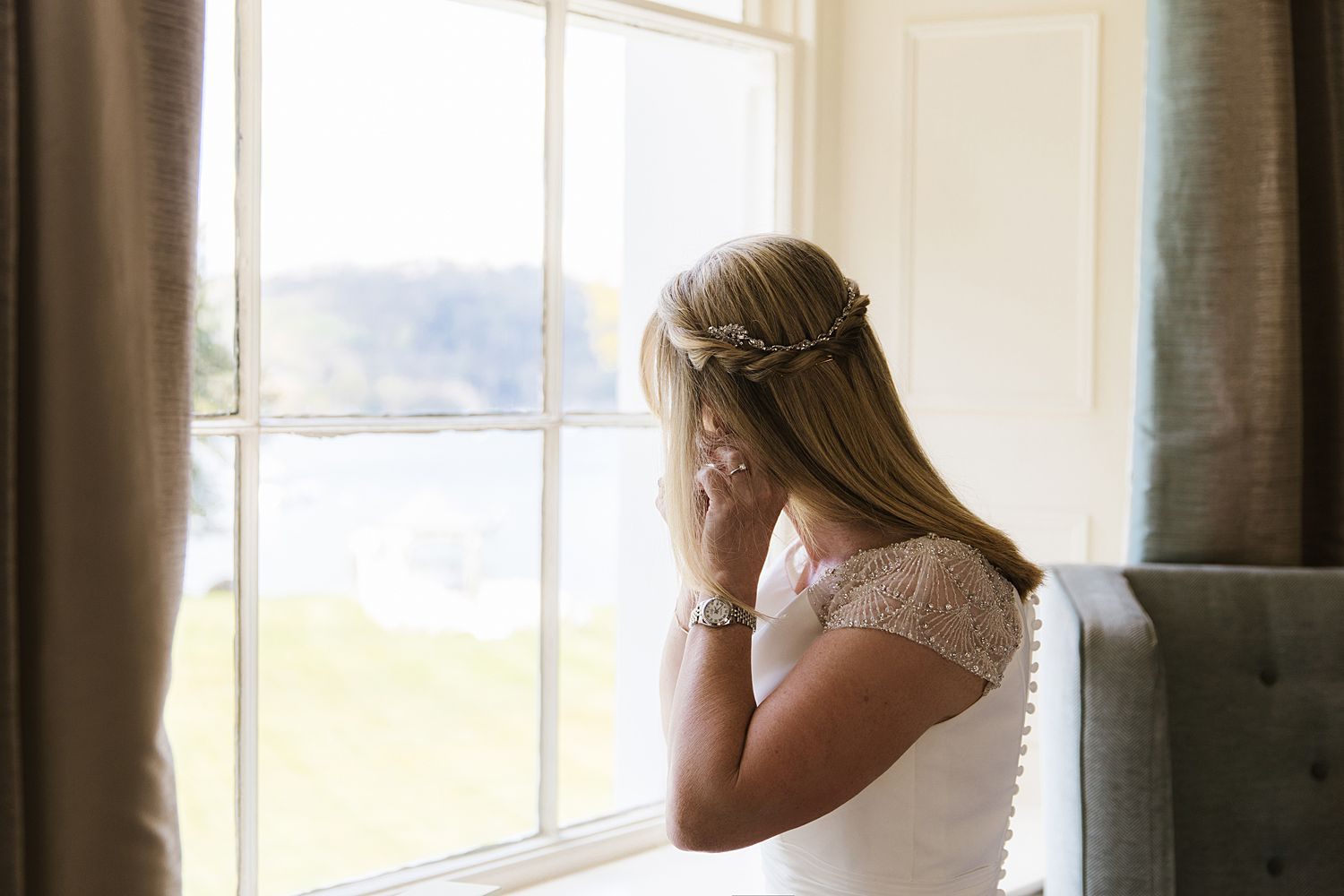 Bride puts in earrings in front of window at Storrs Hall, Bowness on Windermere