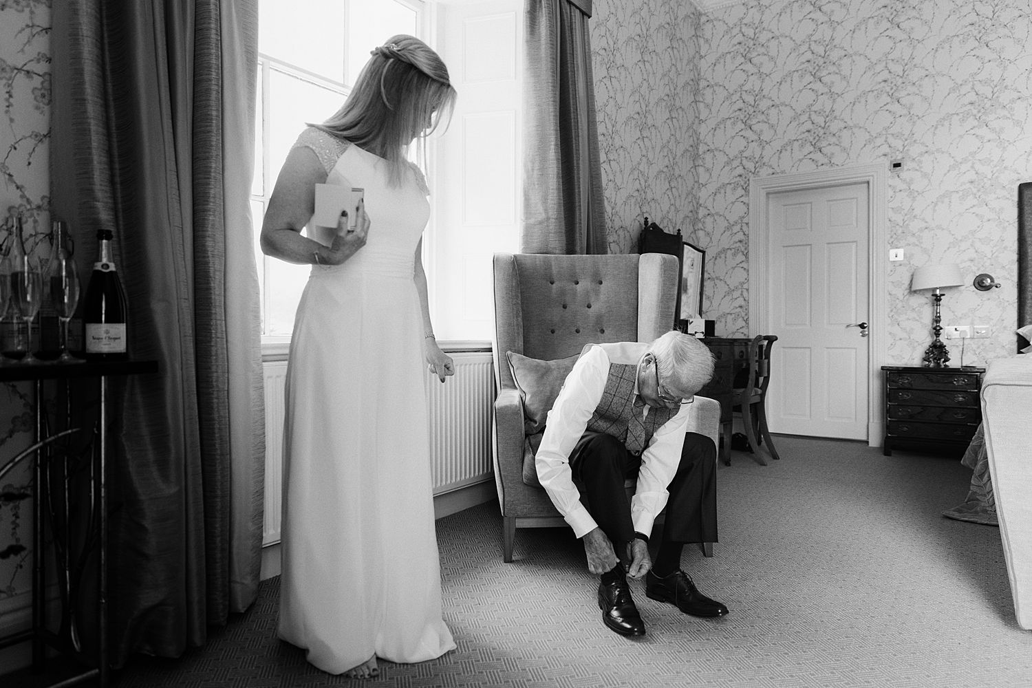 Bride watching dad fastening shoes at Storrs Hall wedding
