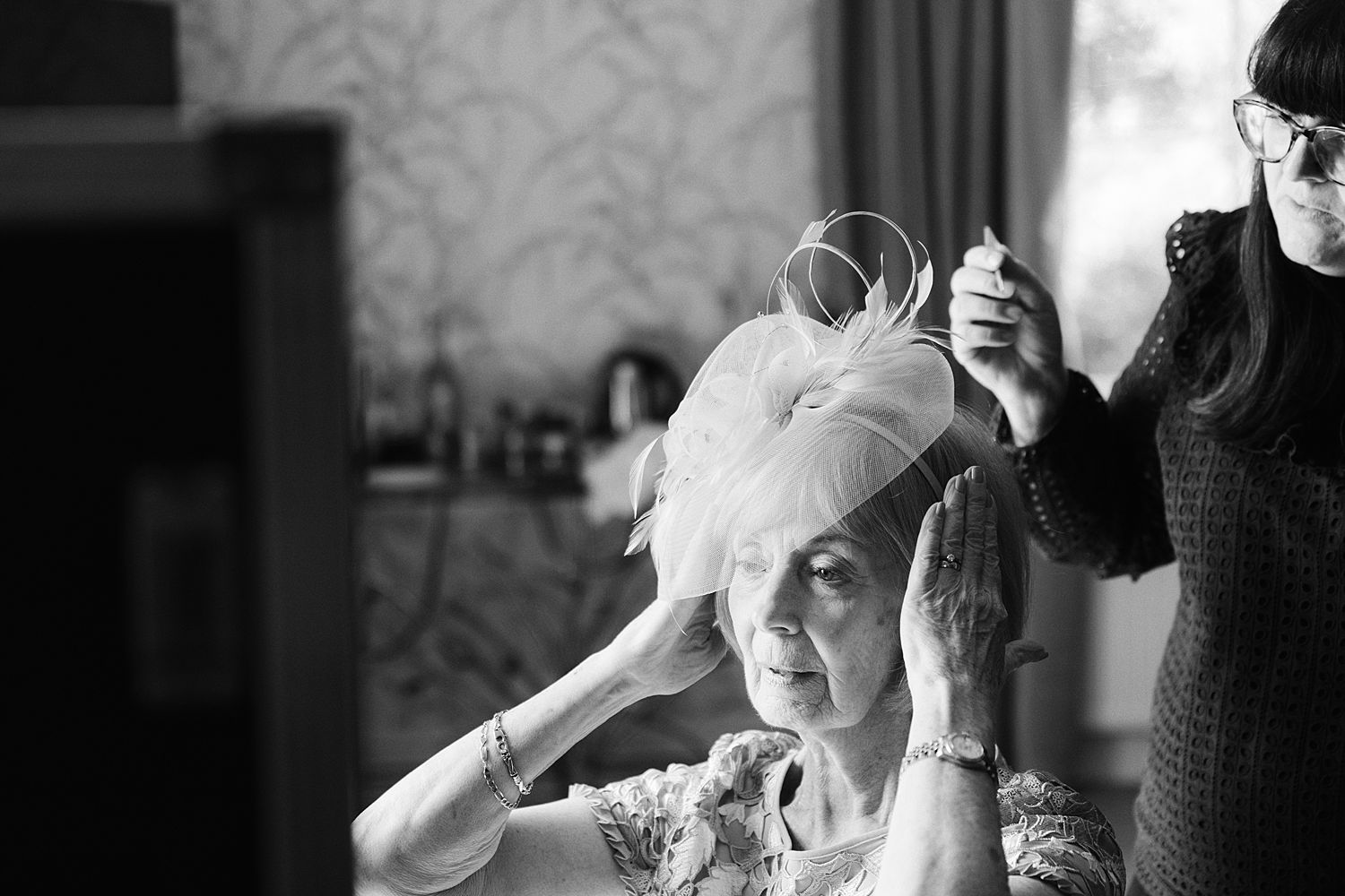 Mum has her fascinator pinned in by Lake District make up artist Lucy Pearson at Storrs Hall, Windermere