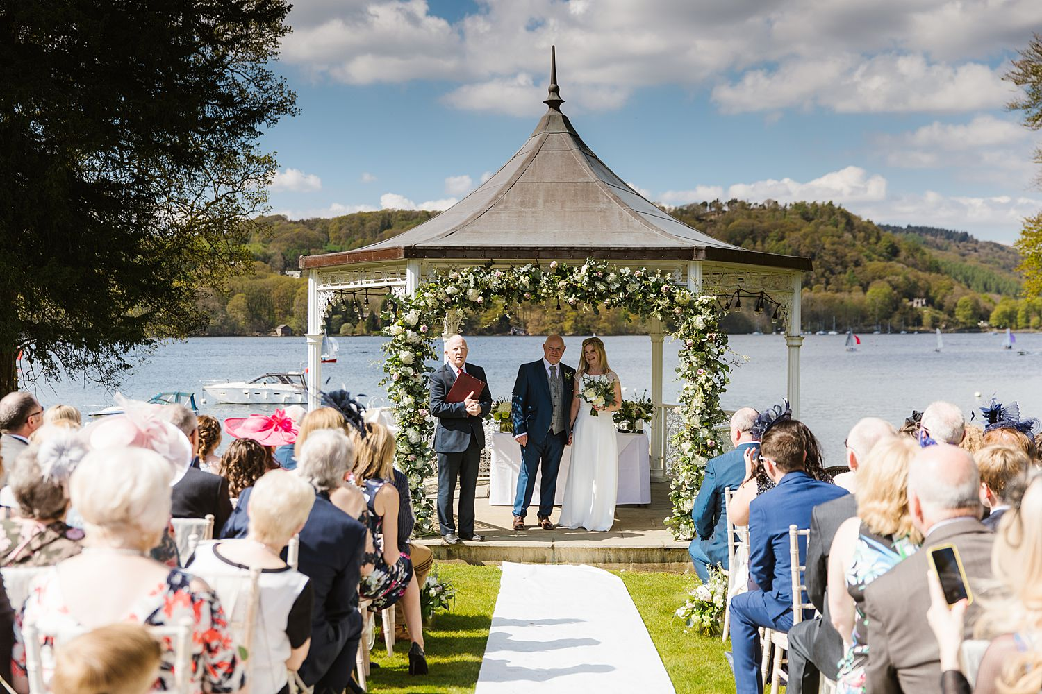 Bride and groom in front of decorated gazebo, with view of Lake Windermere in background, Lake District wedding venue, Storrs Hall