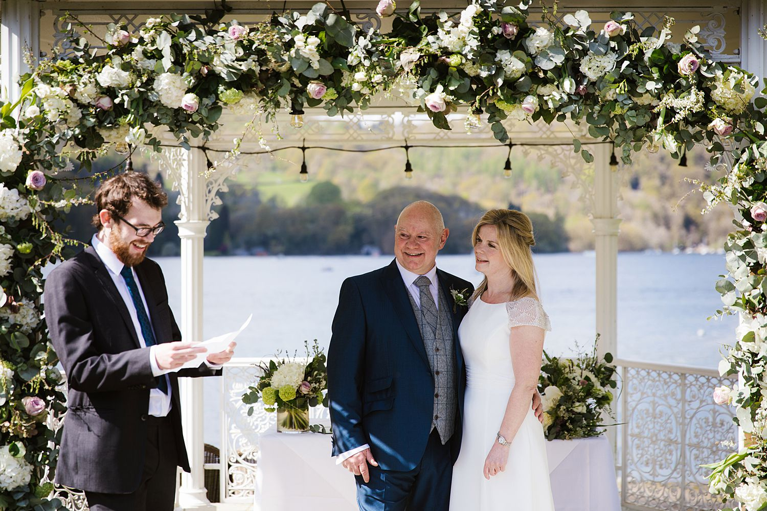 Bride and groom in outdoor ceremony at Storrs Hall hotel, overlooking Lake Windermere