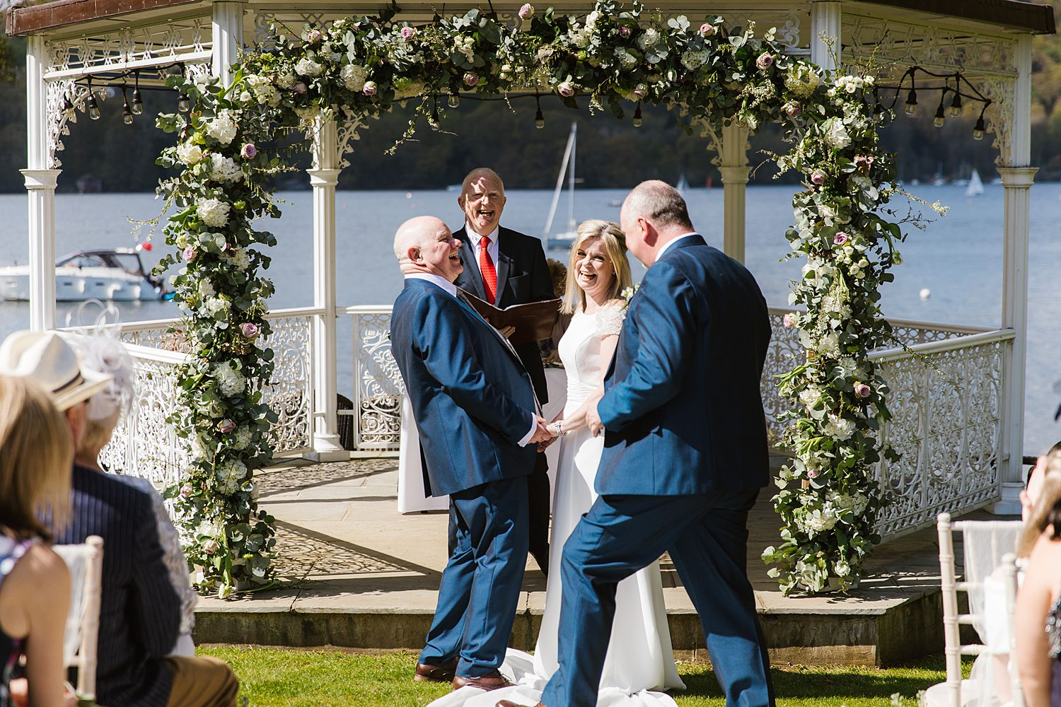 Best man, bride and groom share a joke in outdoor ceremony at Storrs Hall hotel wedding venue, overlooking Lake Windermere