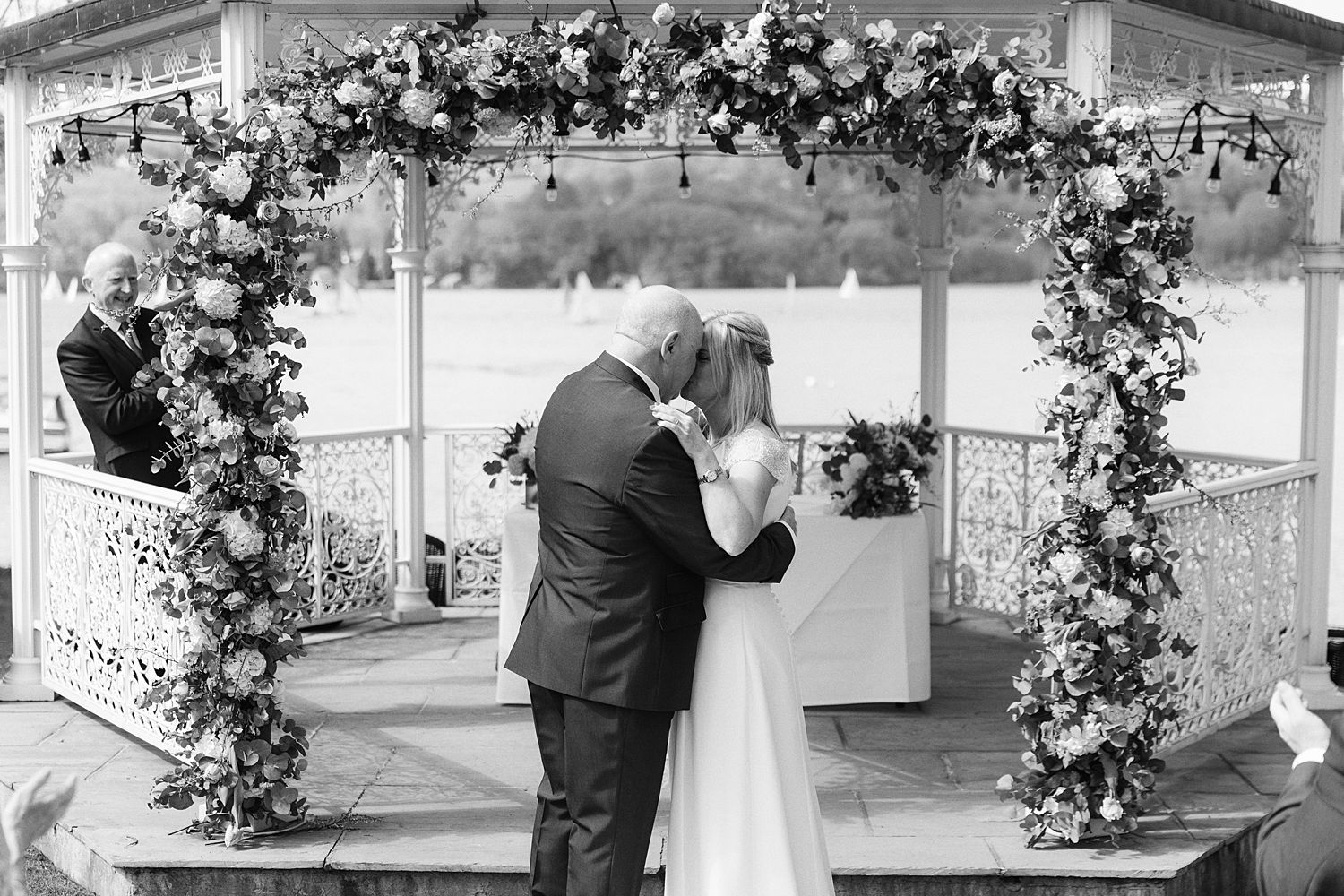 bride and groom share a kiss in outdoor ceremony overlooking Lake Windermere, at Storrs Hall, Bowness on Windermere